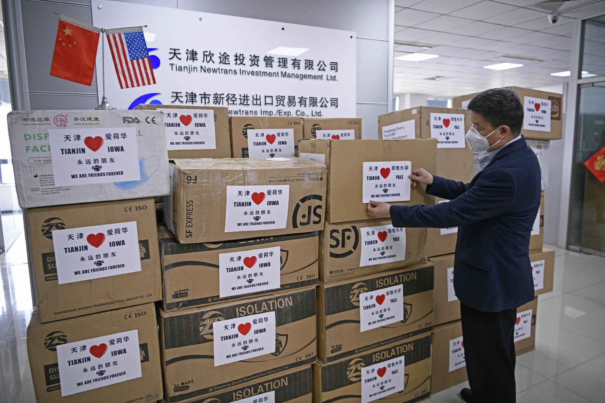 A worker arranges boxes of medical supplies, including 1,000 KN95 masks, 2,000 surgical masks, 100 protective suits and so on