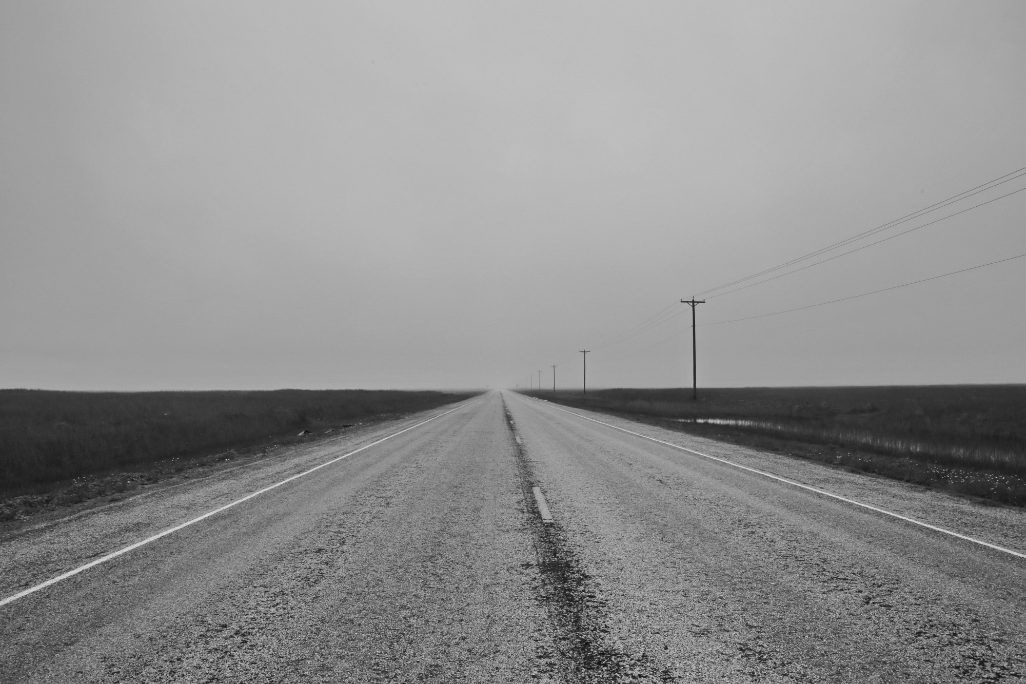 Road, surrounded by a flat terrain, heading off into the distance. Black and white photo.