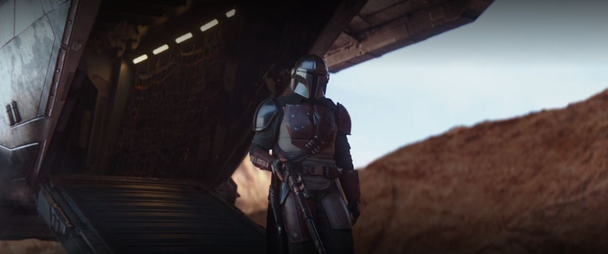 The Mandalorian in a full suit of armor descends from a Jawa ship in a desert