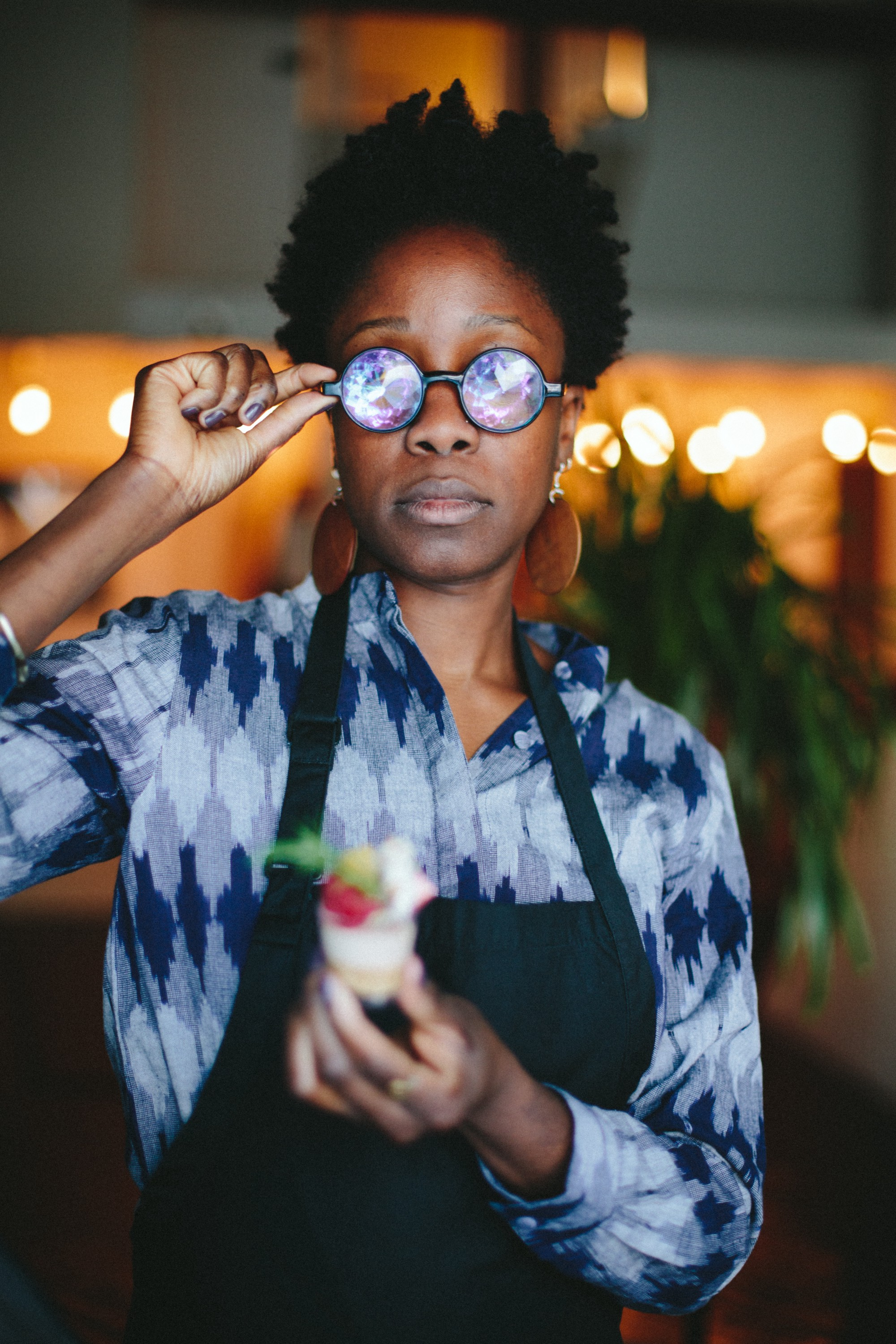 Yewande Komolafe wearing round glasses with iridescent lenses, holding a blurry dessert item.