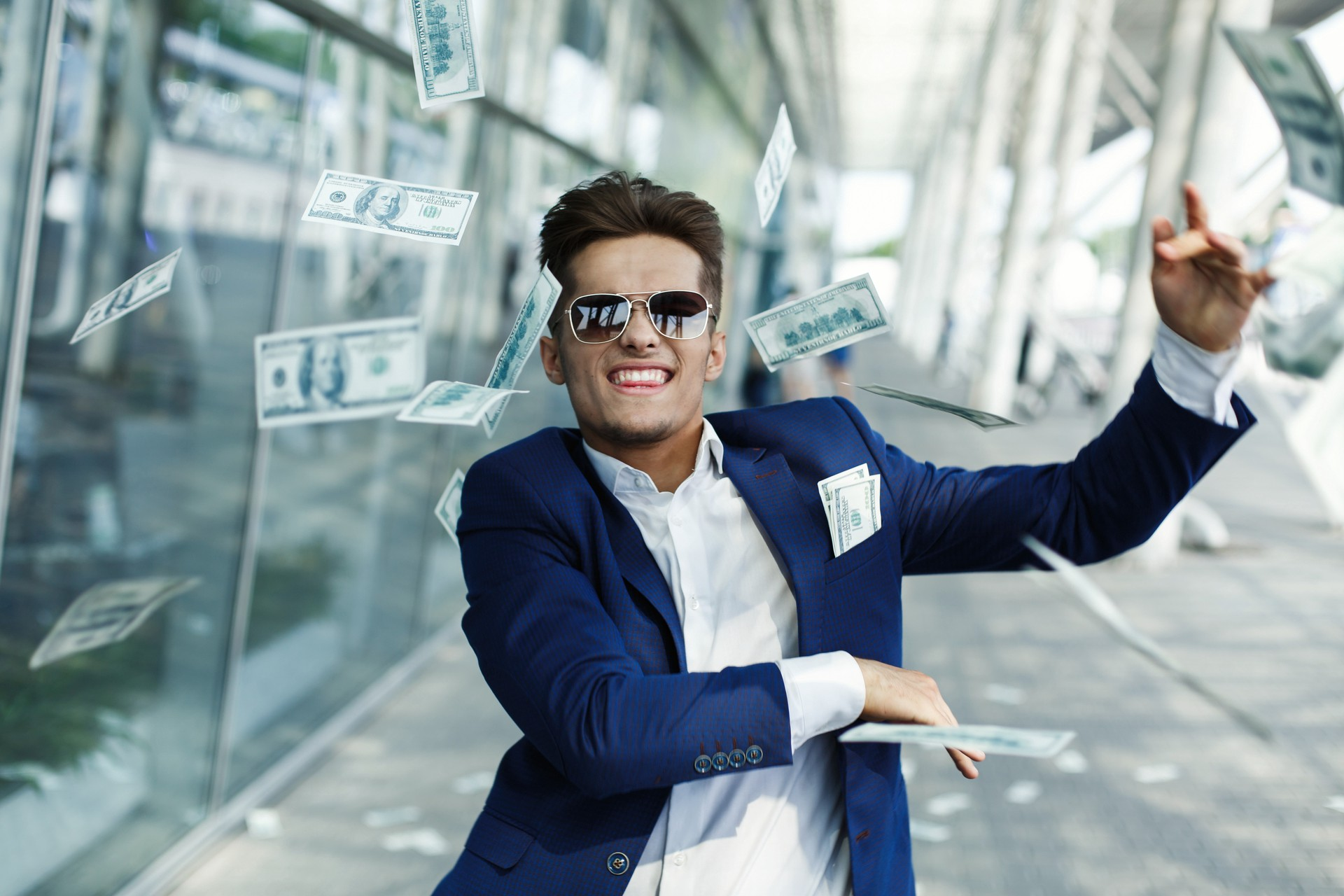 Excited young rich man walking on the street while throwing money away