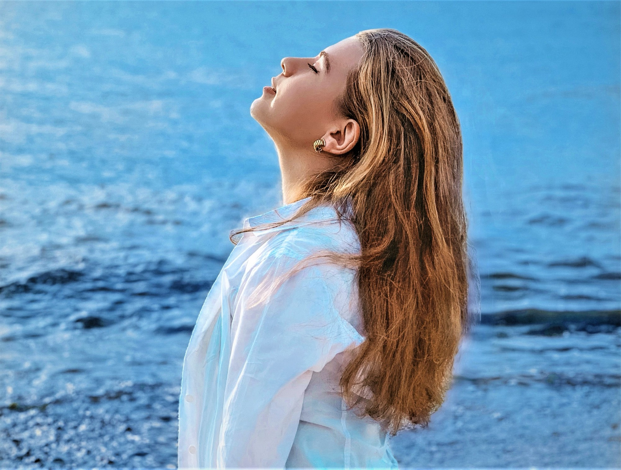 profile of girl with long brown hair wearing white long sleeve shirt with eyes closed and head tilted up with blue ocean behind her