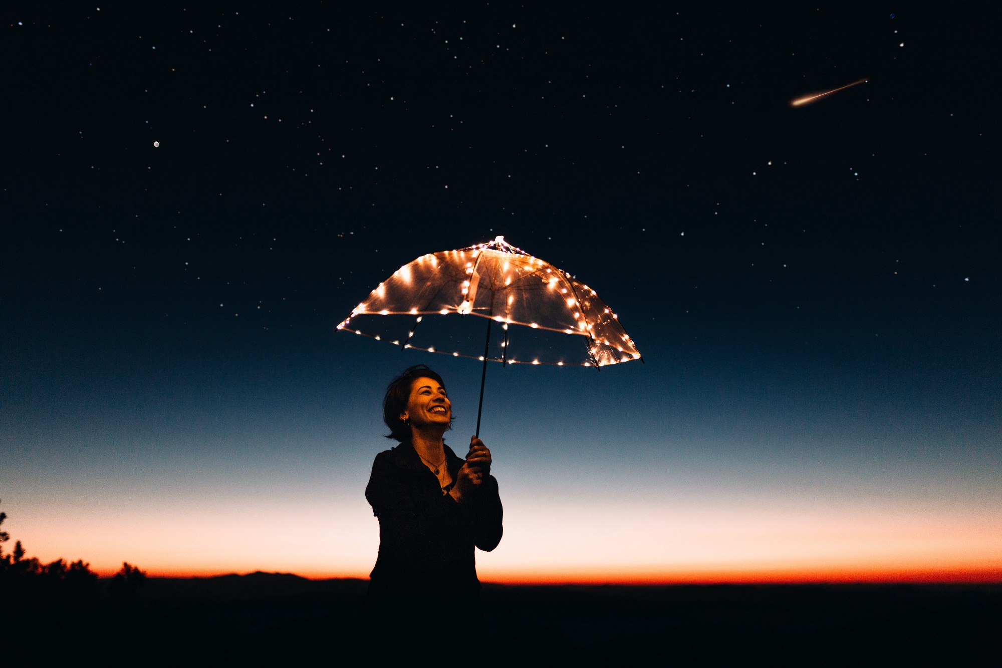 Woman holding umbrella with lights against a night sky.