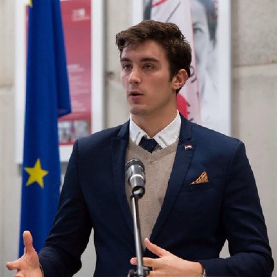 Luka Ignac giving a speech in front of the E.U. flag.