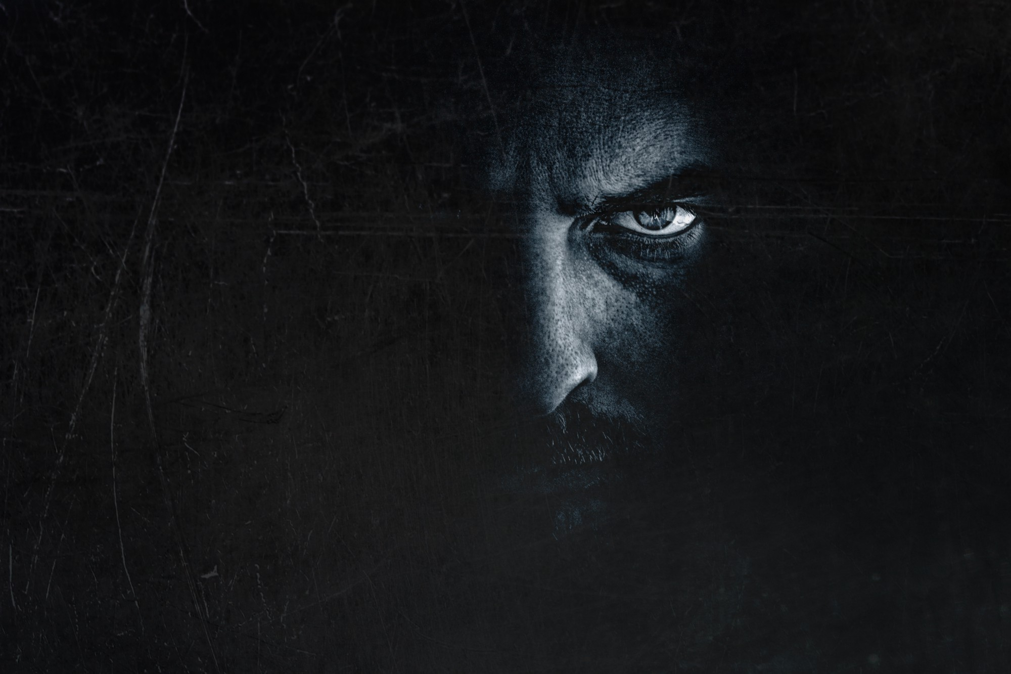 Dark portrait with half of a mans face showing in just a little light. He looks angry and menacing.