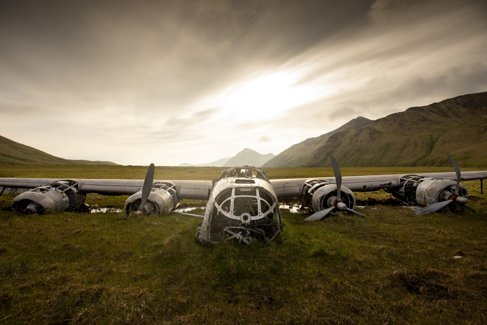 Landscape image showing a large metal aircraft with exposed fuselage and four engines half buried in the green tundra with mountains in the background.