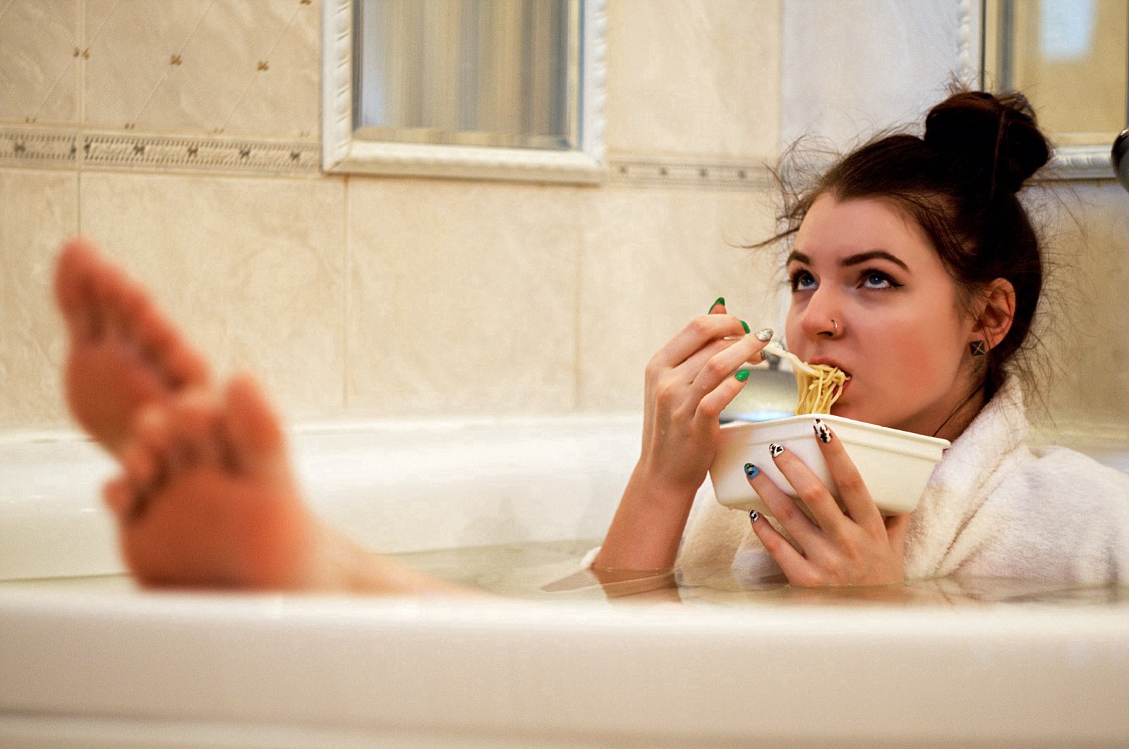 Woman sitting in the bath eating instant noodles out of a plastic container