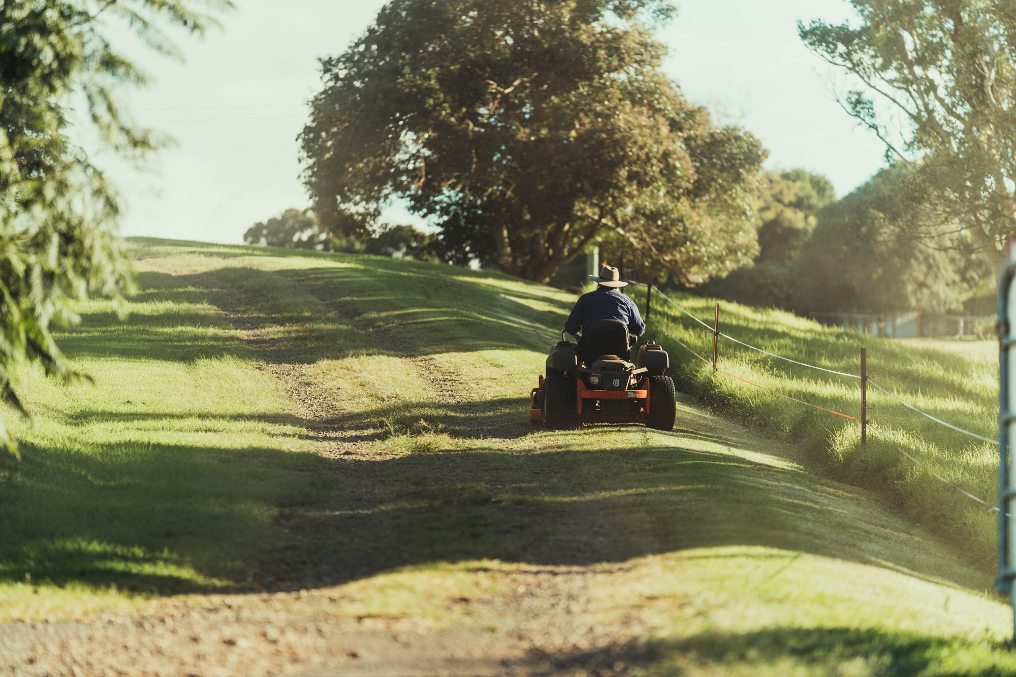 A man on a riding lawn mower, cutting grass between a fence and a driveway.