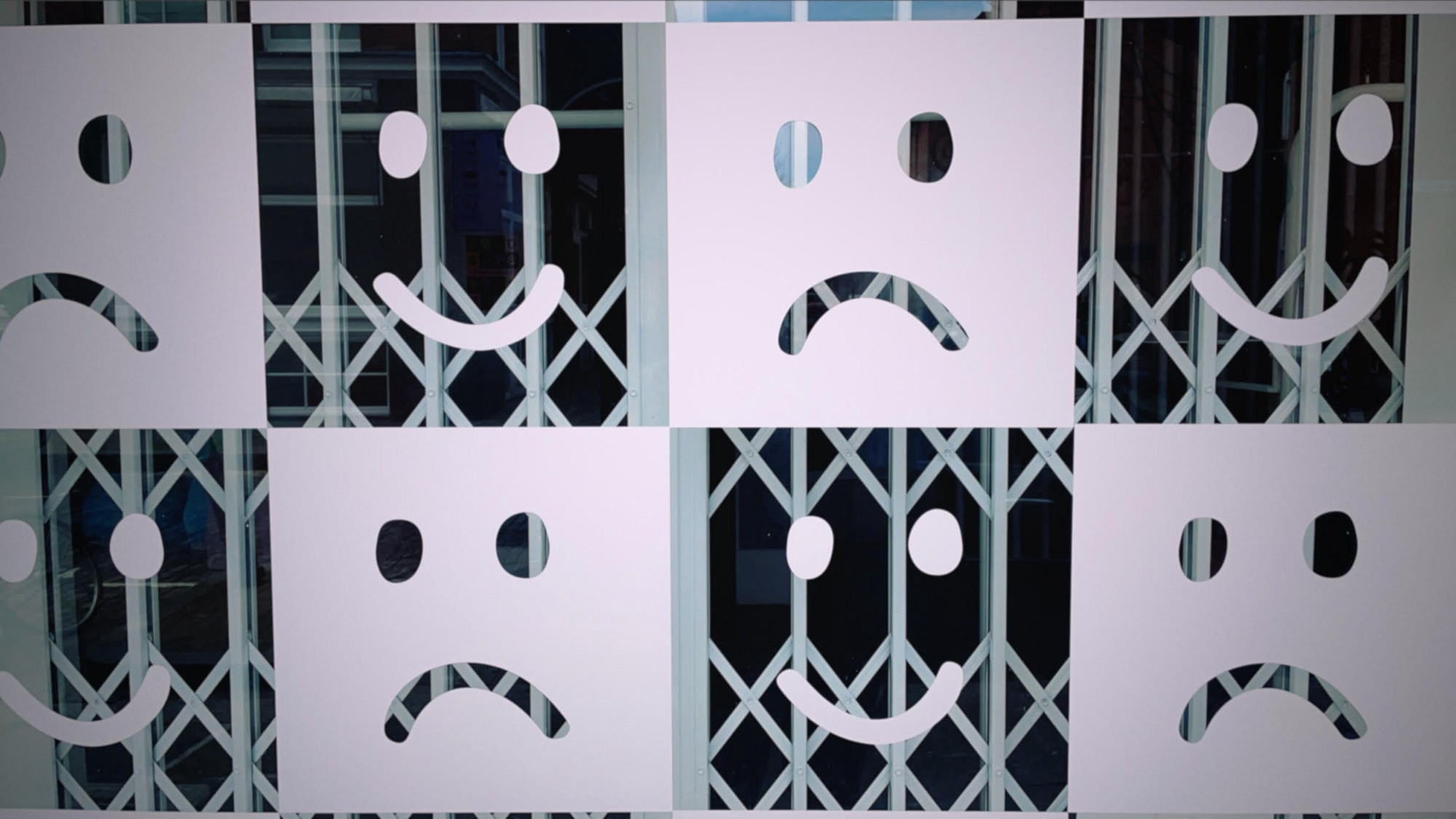 A shop window painted with alternating smiling faces and frowning faces, taken on the photo app Dispo.