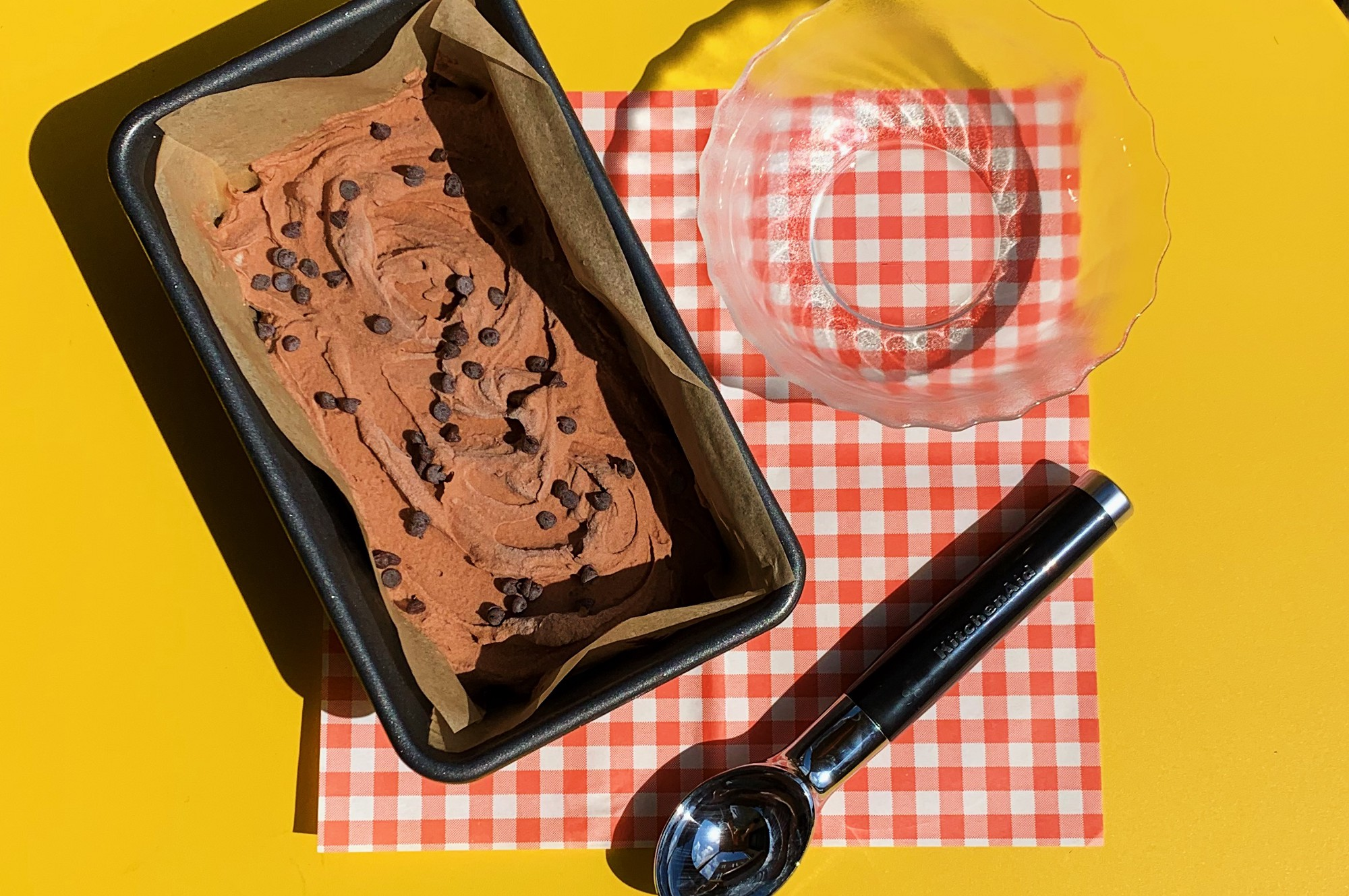 A loaf pan lined with parchment paper and filled with chocolate chocolate chip ice cream next to an ice cream scoop & a dish.