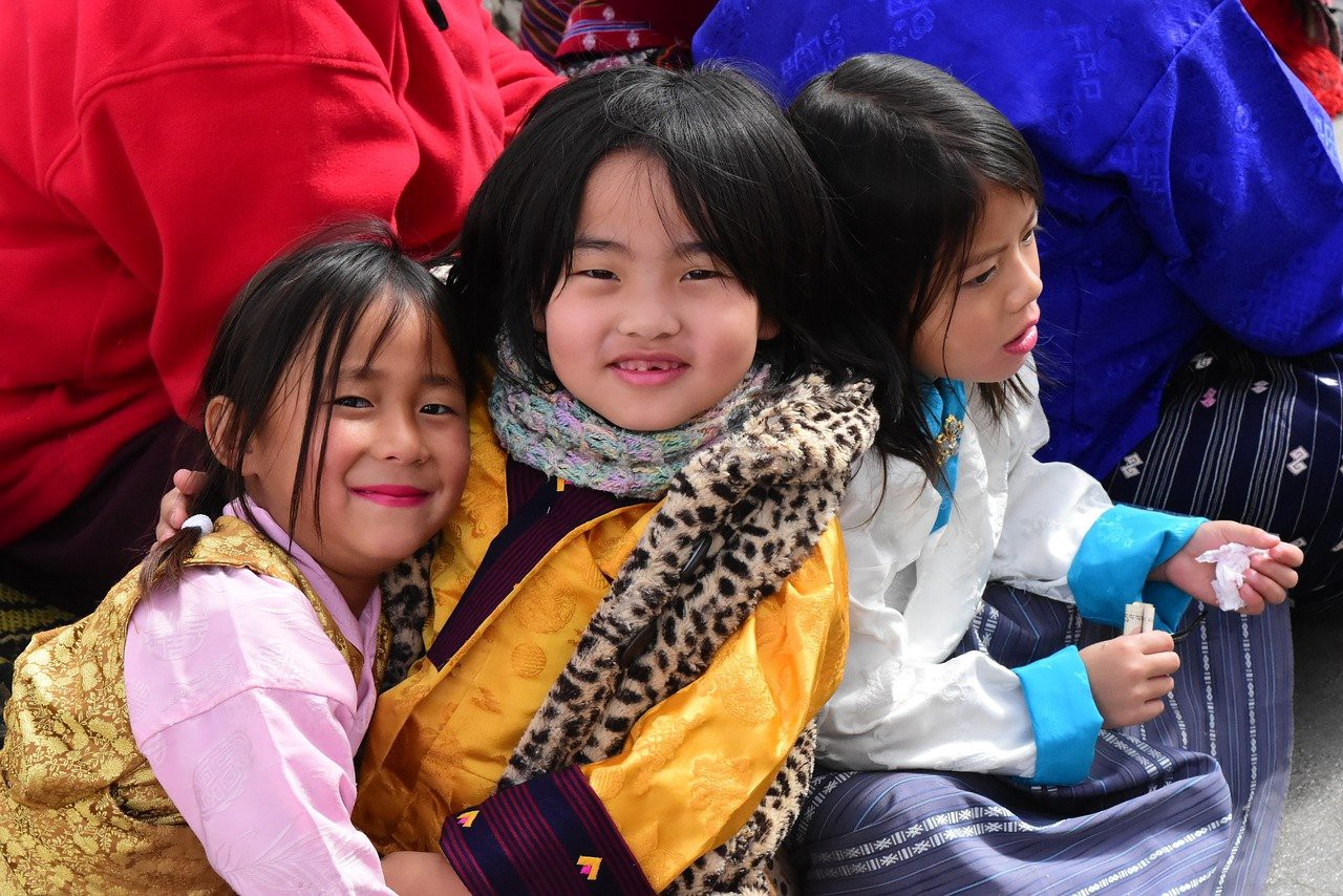 Two small girls in traditional Bhutanese attire at a festival, smiling at the camera.