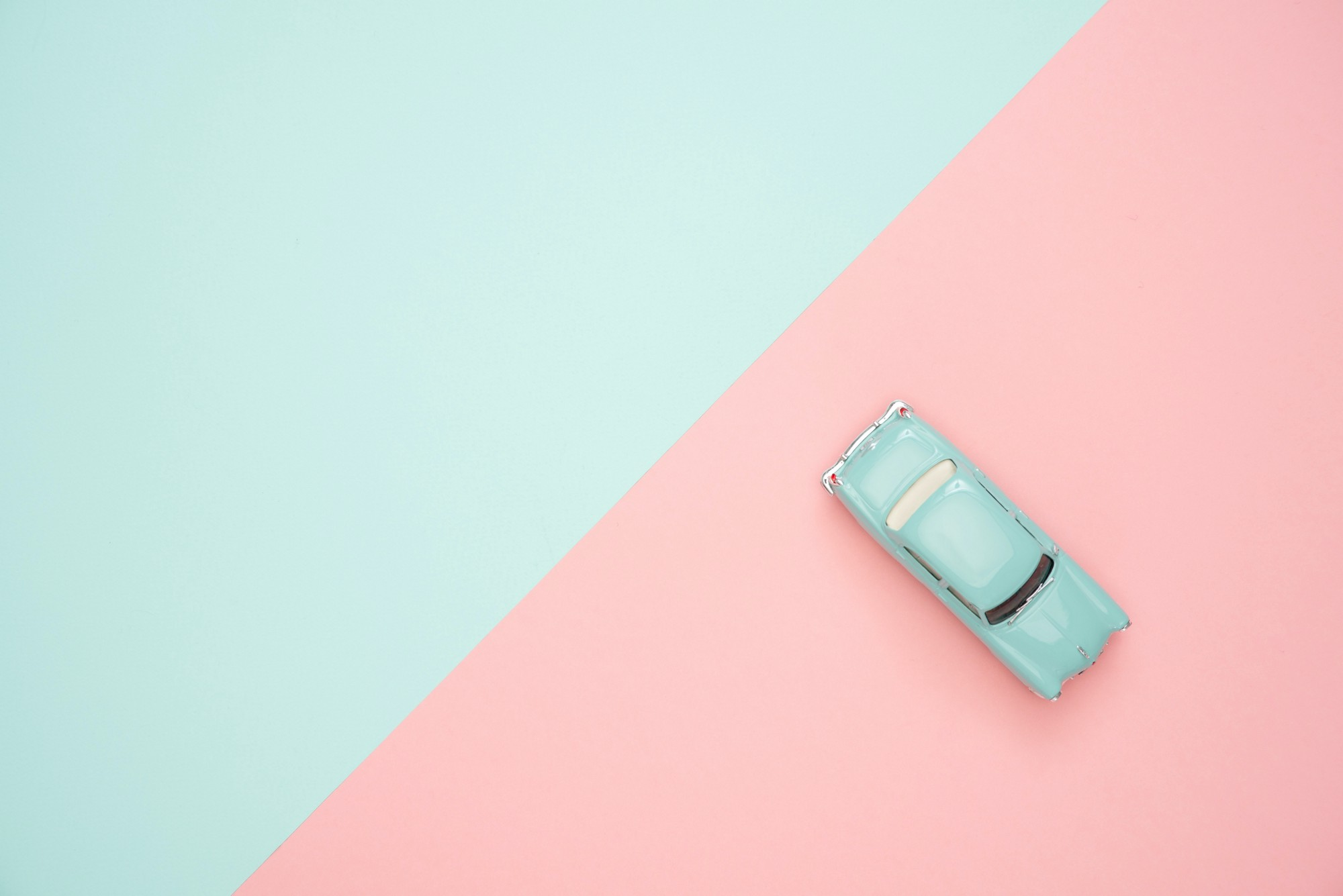 Divide between blue and pink sides of a photo, with a blue toy car on the pink side
