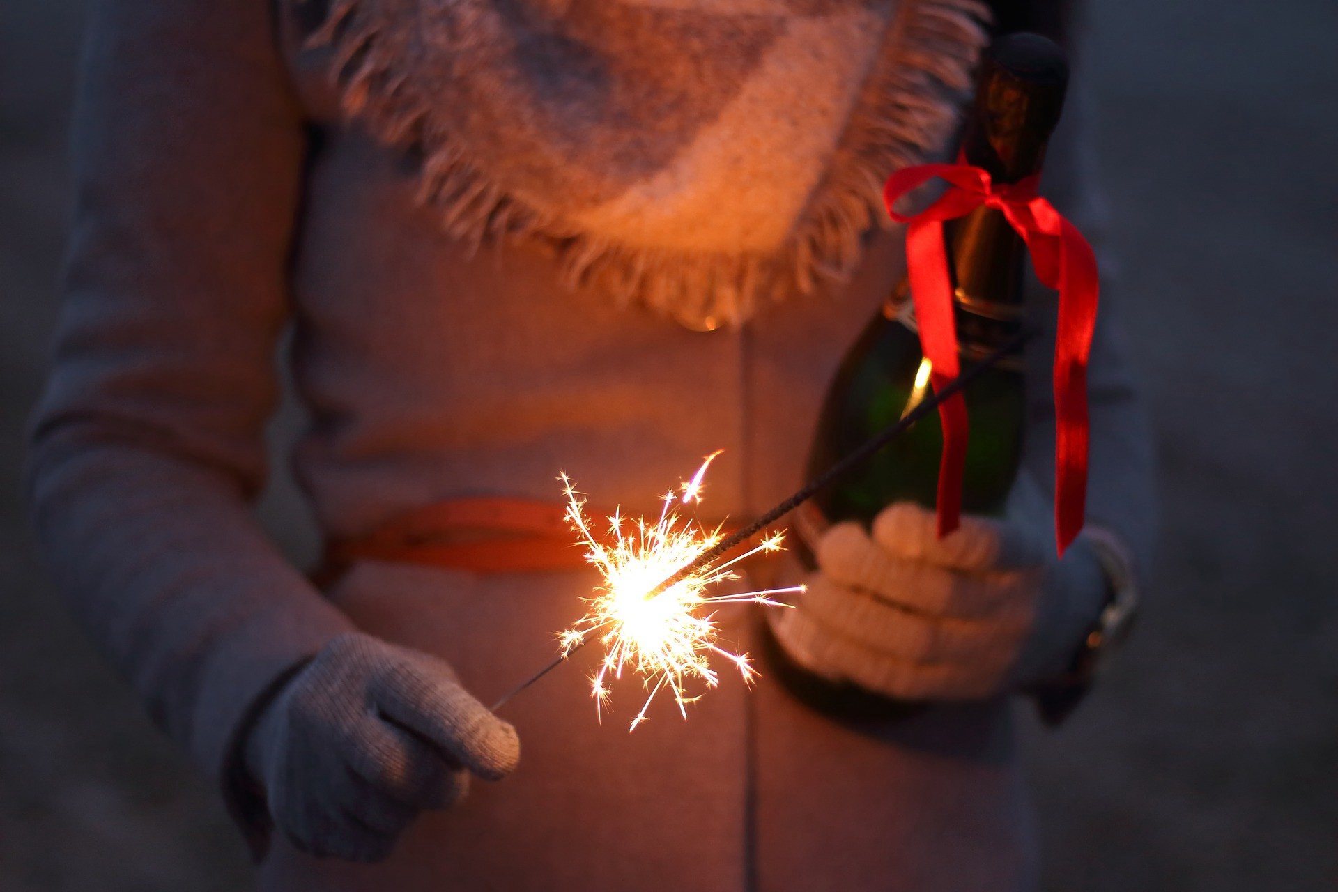 A girl in a warm jacket holding a bottle with a red ribbon on it, wearing gloves. She is holding a lit sparkler