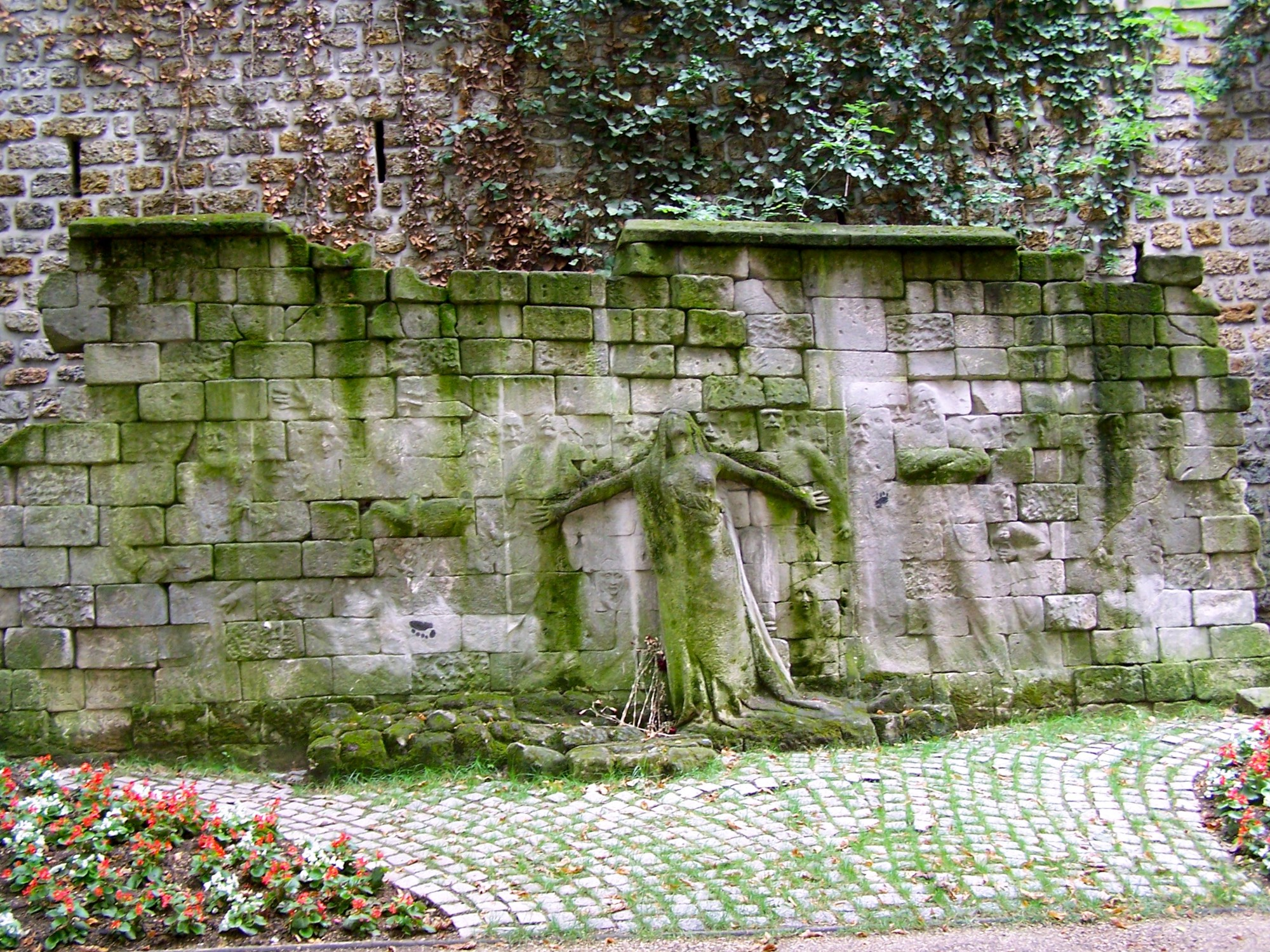 Carved in relief on an old stone wall is a plaintive female figure, arms outreached, eyes skyward, who can be clearly seen. Less visible are the much shallower reliefs, the carvings of people, mostly men with mustaches, who seem to hover around her.