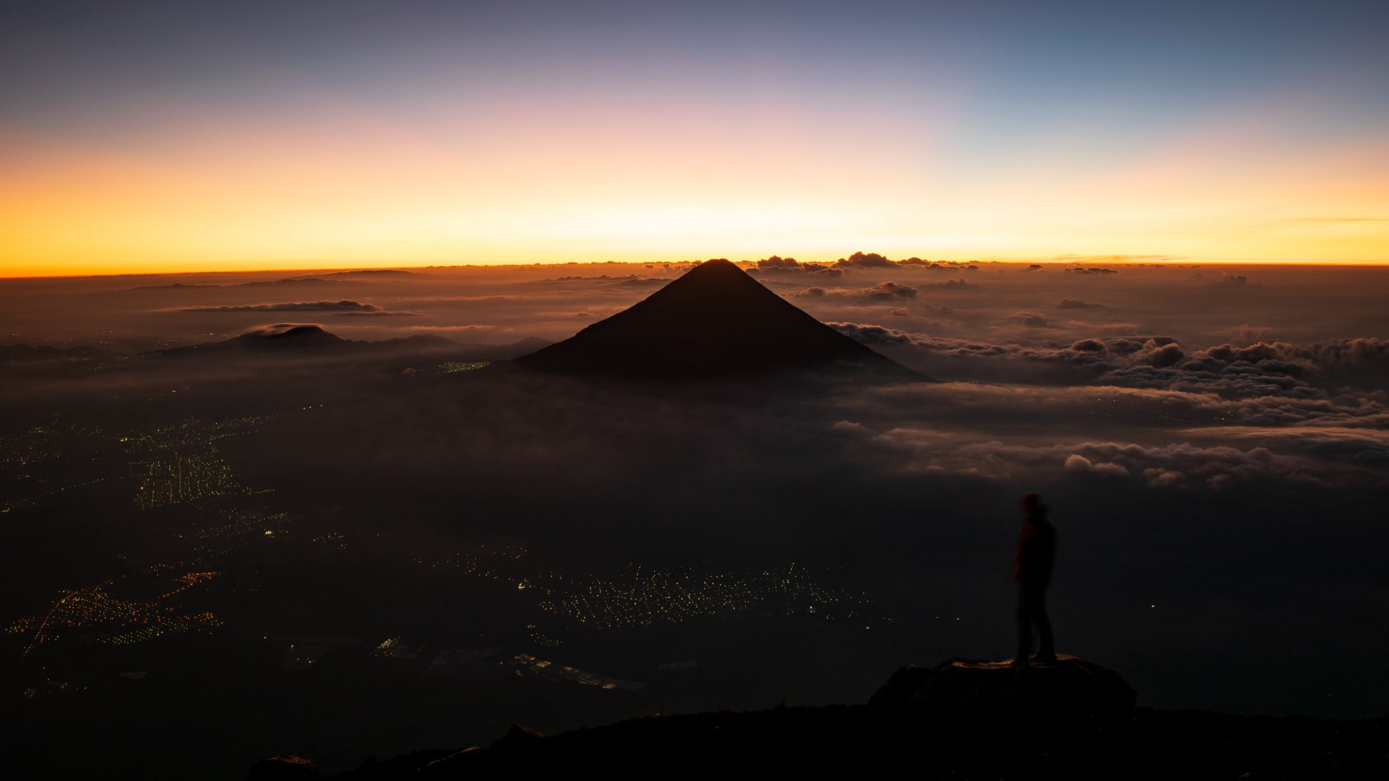 City lights glow under a mountain sunrise-daily transformation