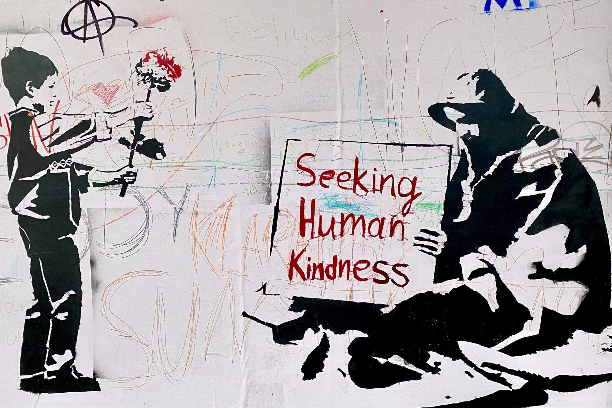 black and white wall art of boy offering flower to man with sign that reads 'seeking human kindness'