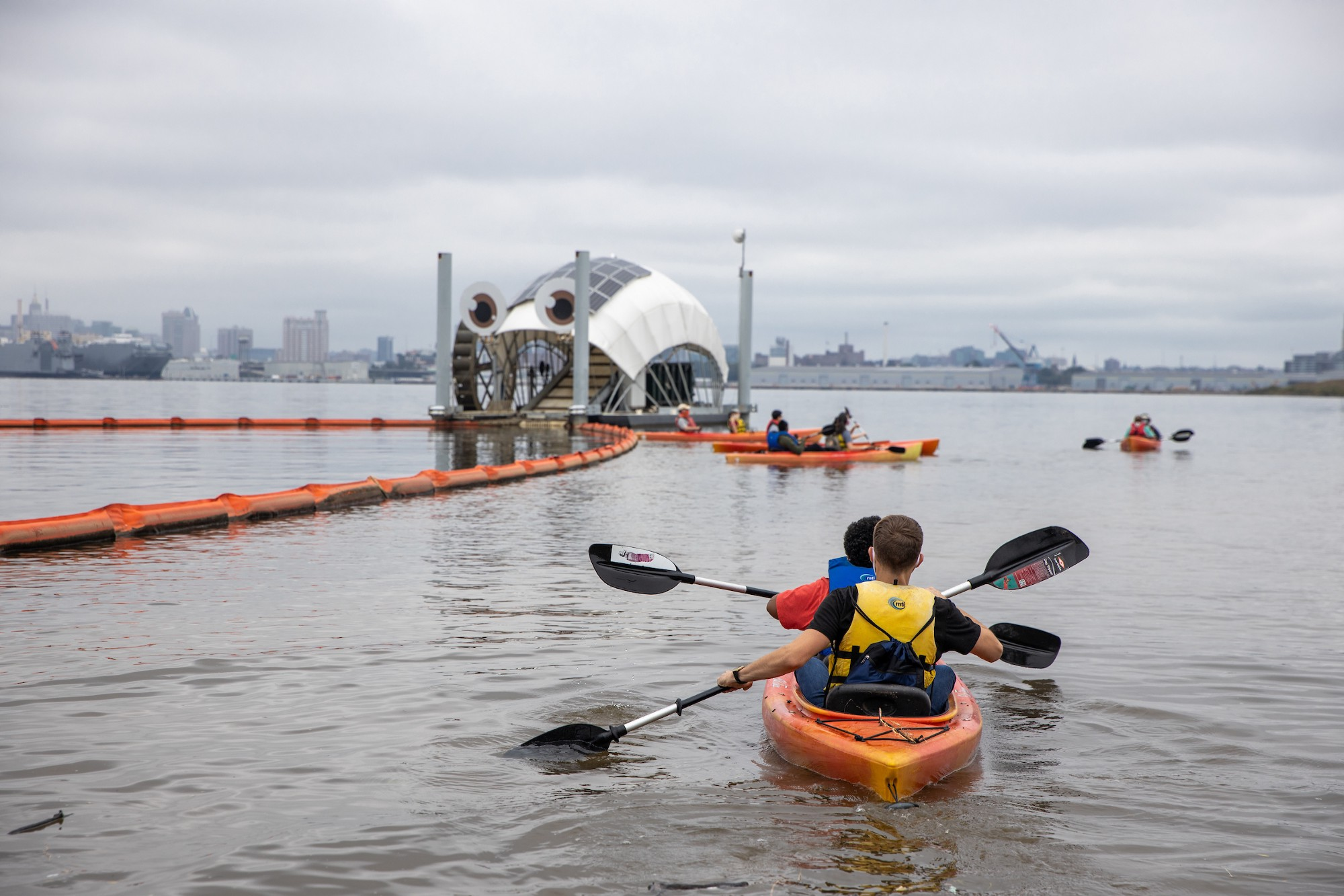 a two person kayak paddles towards a floating structure with eyes and more boaters