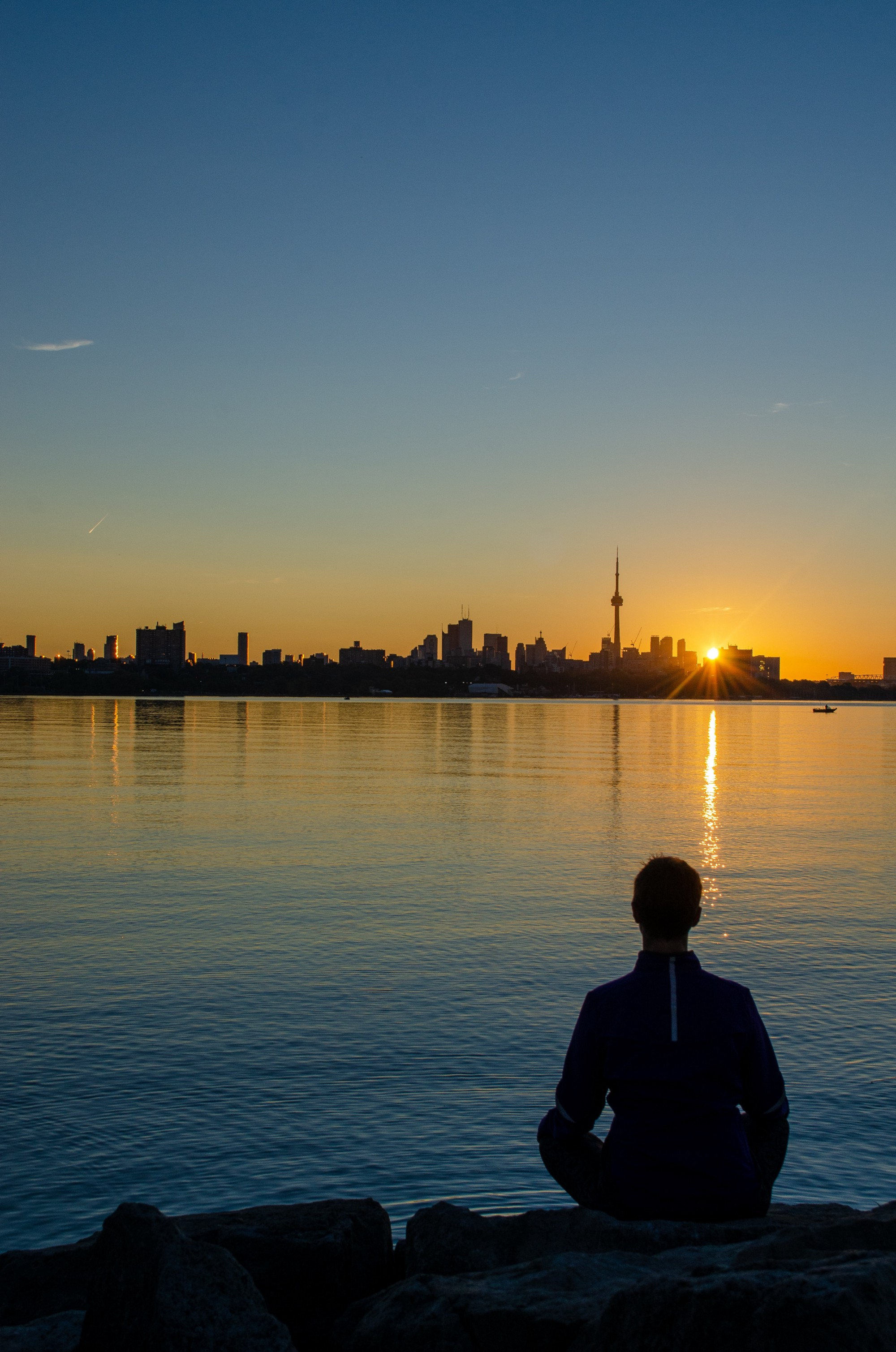 Man meditating next to water with city skyline and sunset in the distance