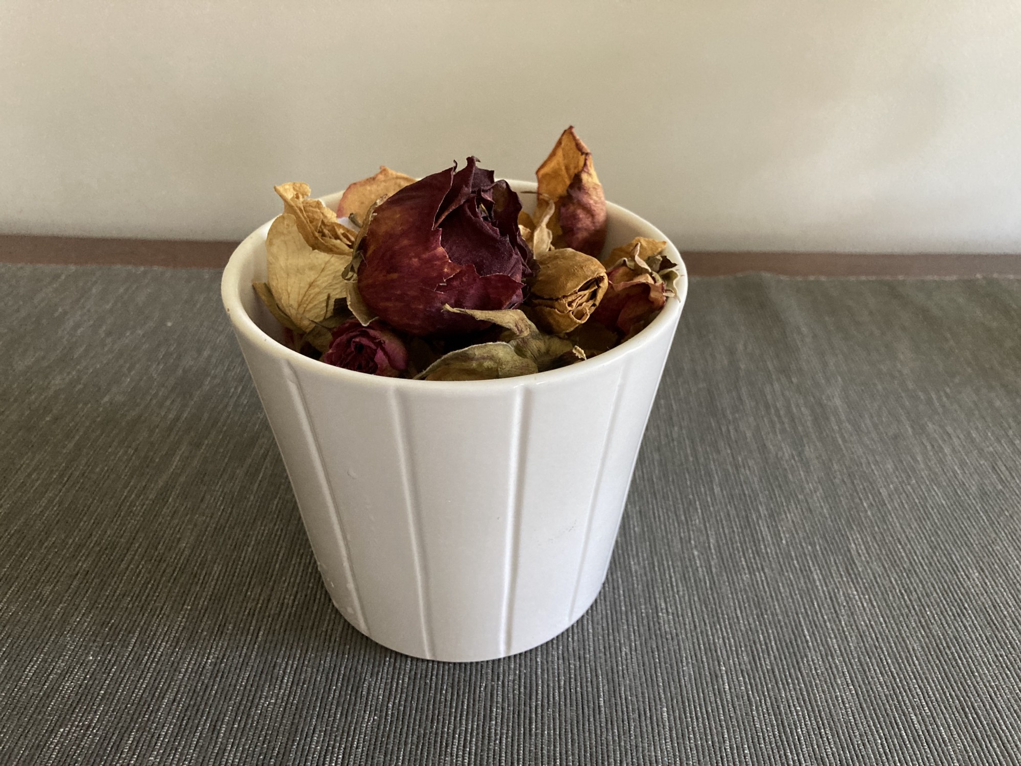 dried red & yellow roses in white cermic pot