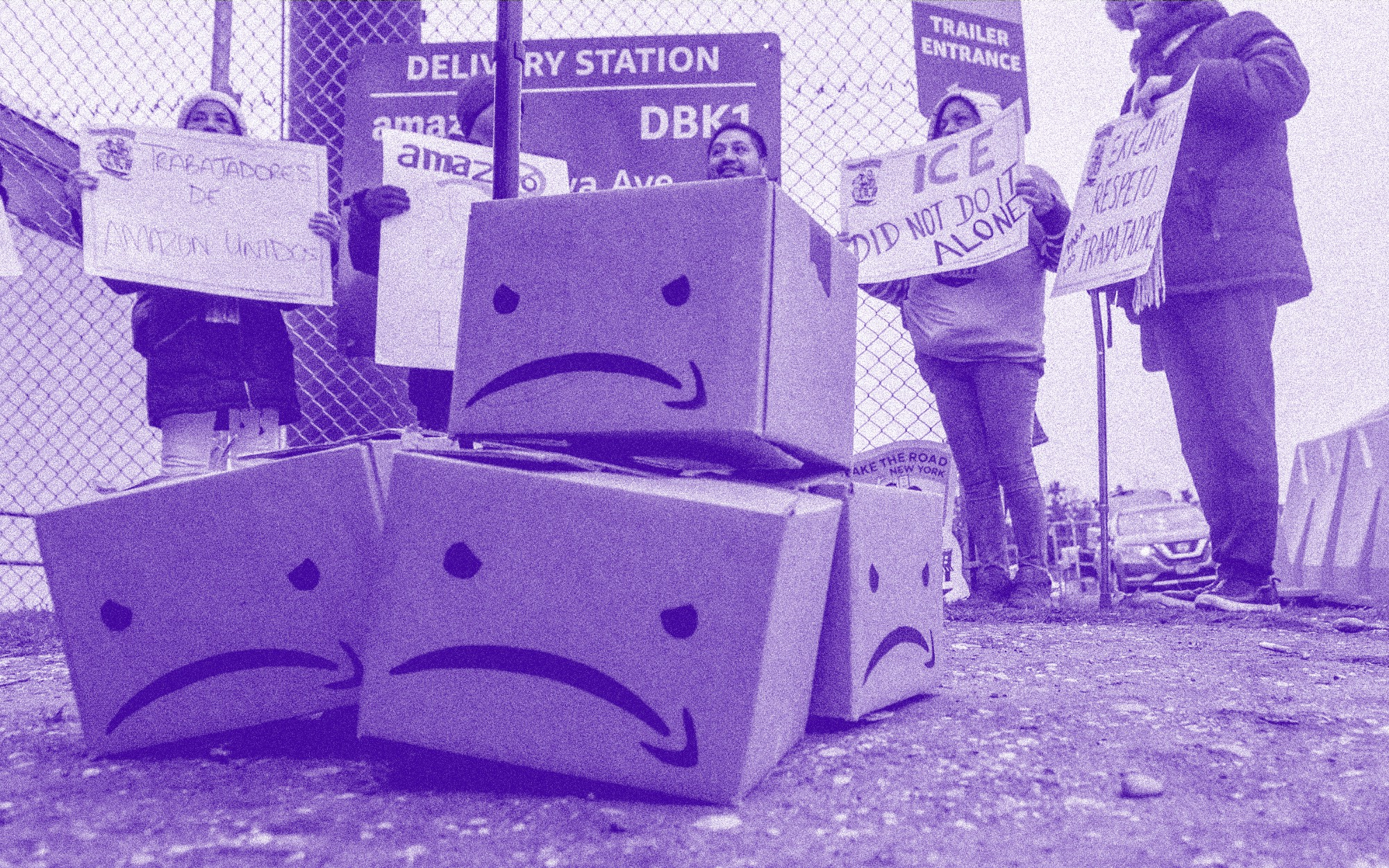 A purple filtered photo of a stack of boxes with an angry Amazon face on them at a protest.