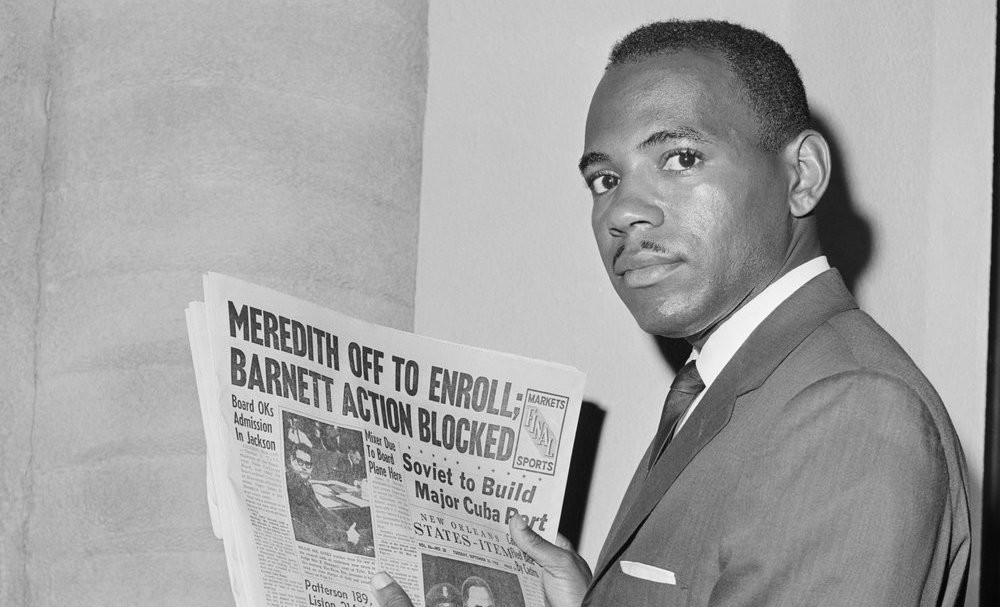 """James Meredith holds a newspaper in 1962 with the caption, """"Meredith Off to Enroll; Barnett Action Blocked."""" Photo Credit: Be"""
