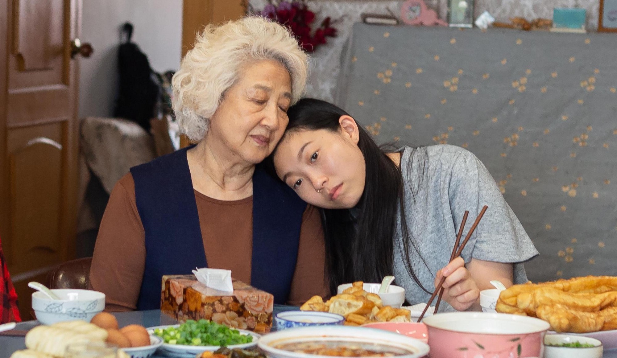 A young Chinese American woman rests her head against the shoulder of an elderly Chinese woman