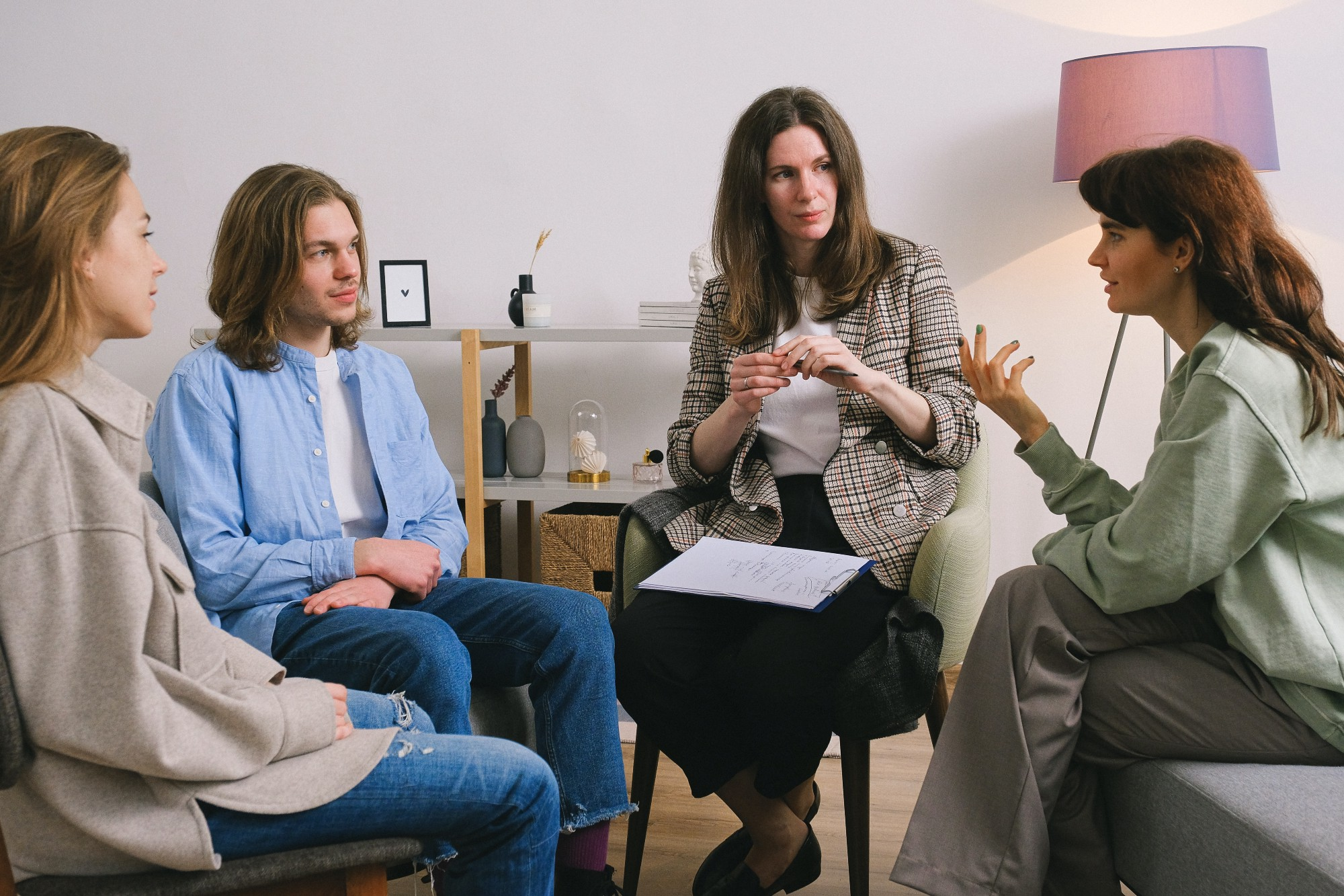 Woman explaining herself to two other women and one man.