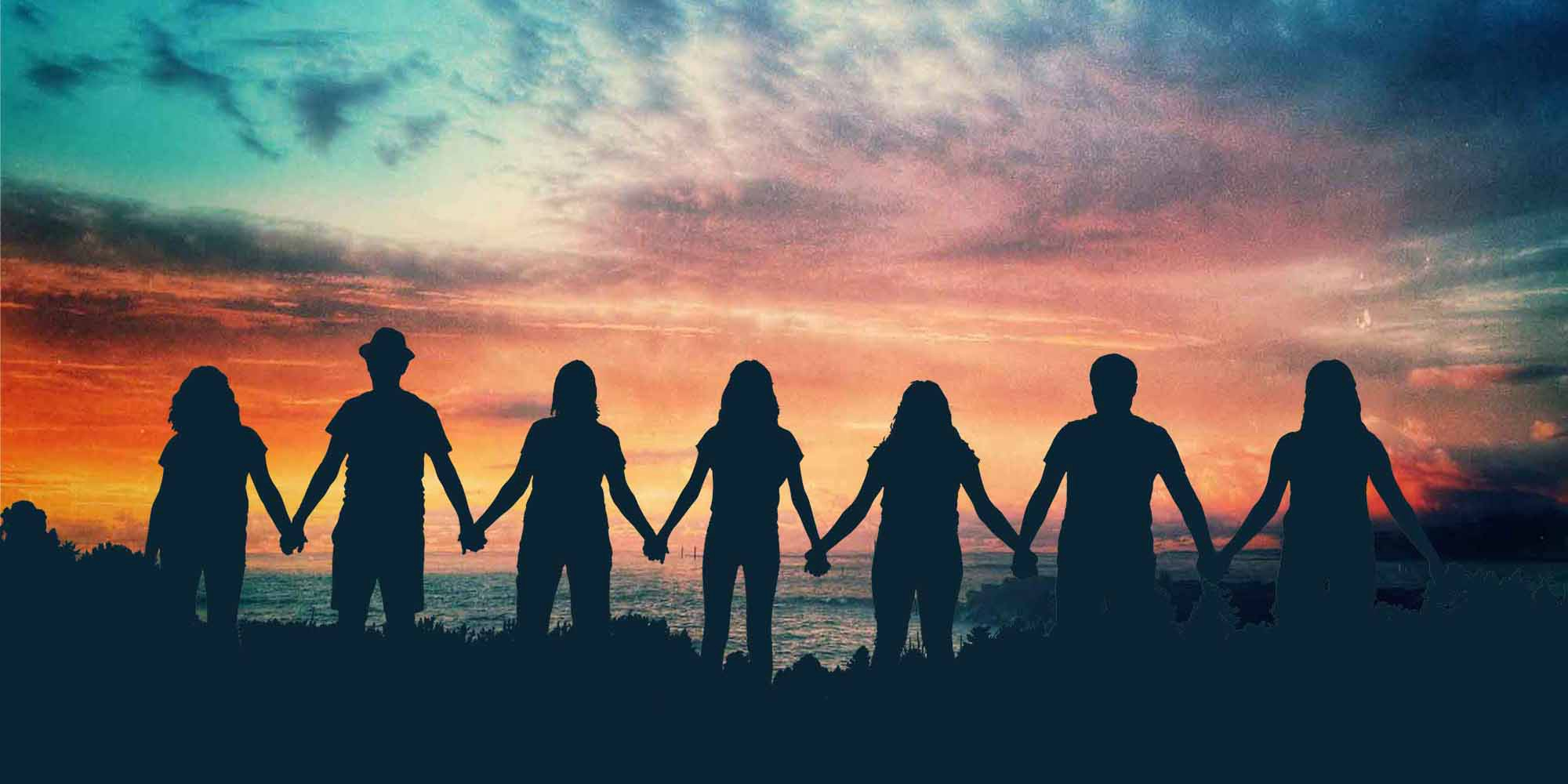 People holding hands in silhouette against sunset sky
