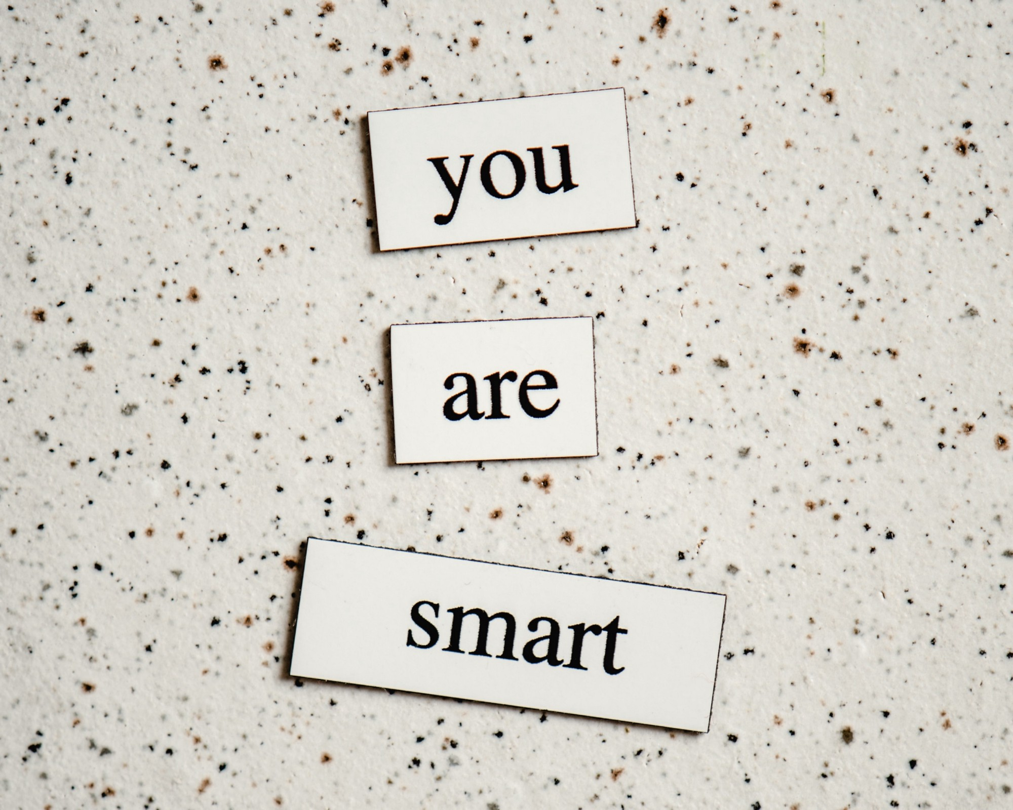 """3 blocks on a marble surface saying """"you are smart"""""""