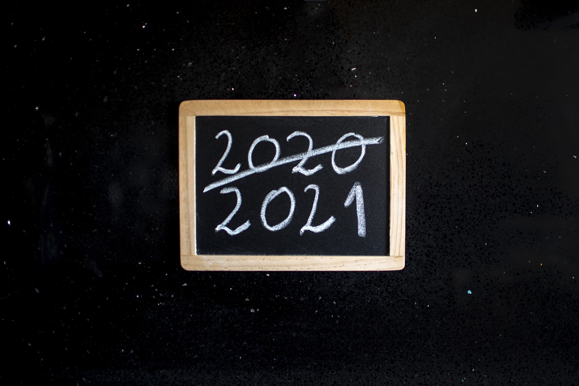 "Black Board showing ""(Bye) 2020, (hello) 2021"" written on it by white chalk."