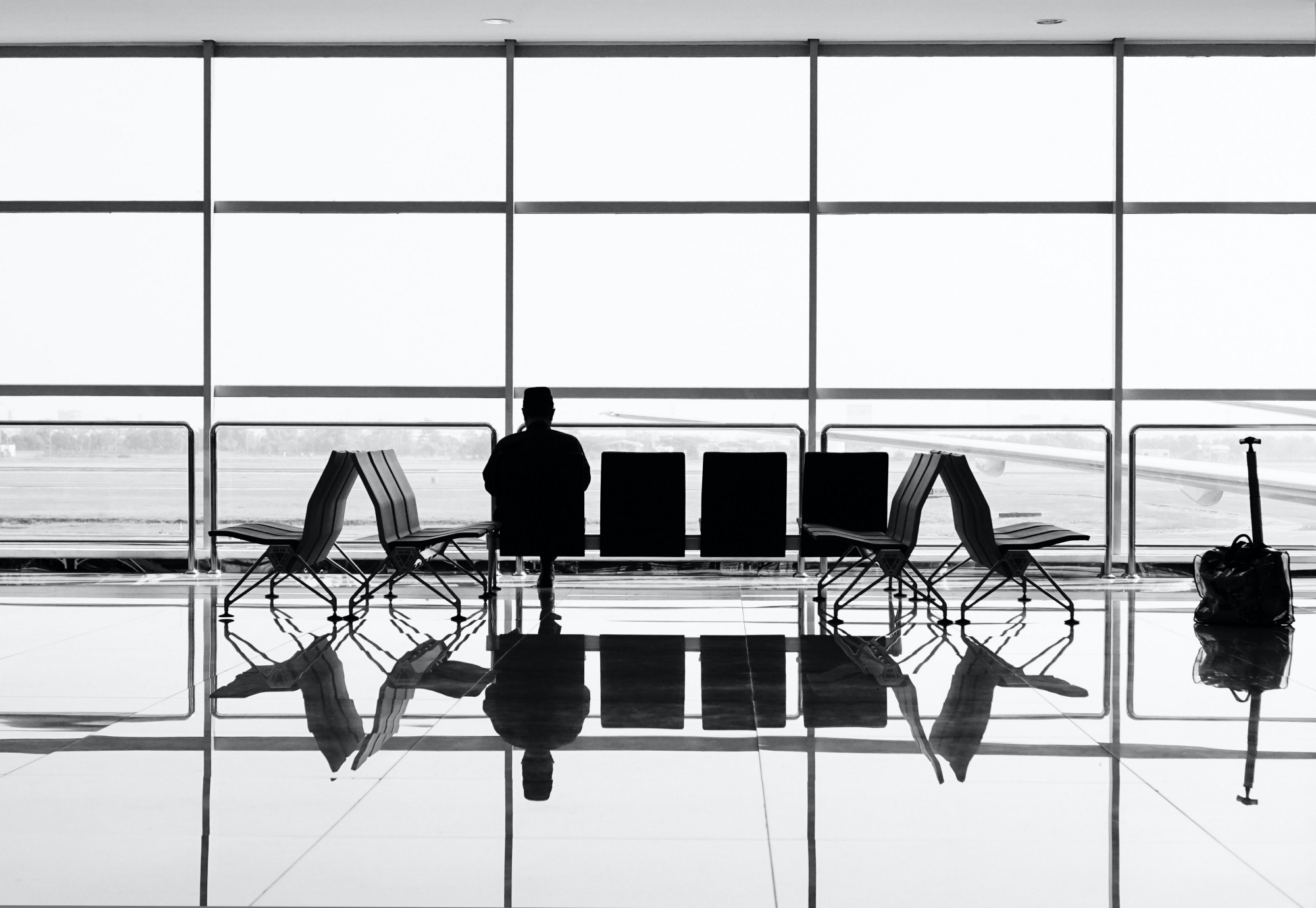 A photo of a man sitting in a gate terminal of an airport