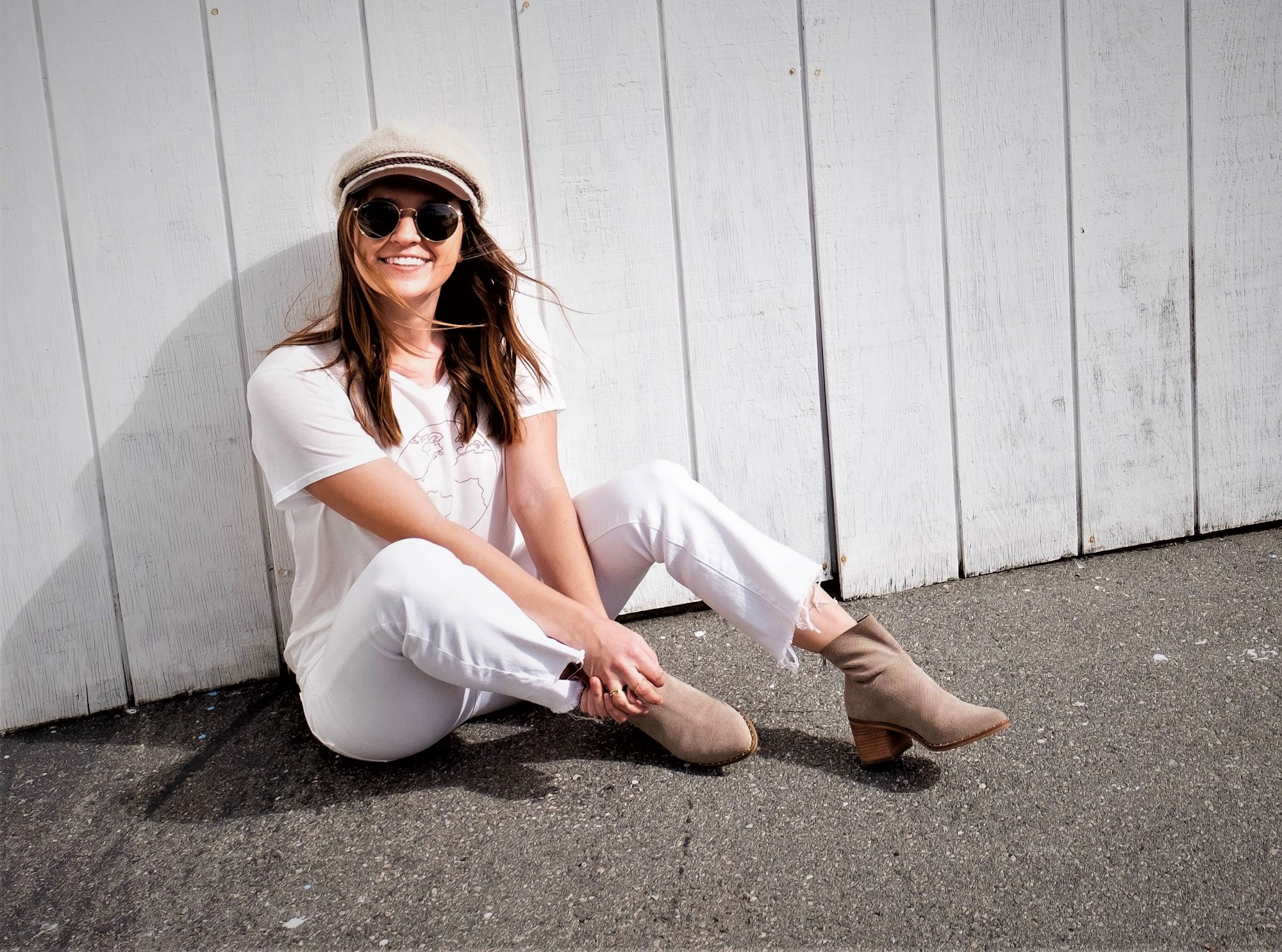 smiling girl with long brown hair wearing sunglasses white top and pants and tan boots and hat sitting on ground leaning against white board wall