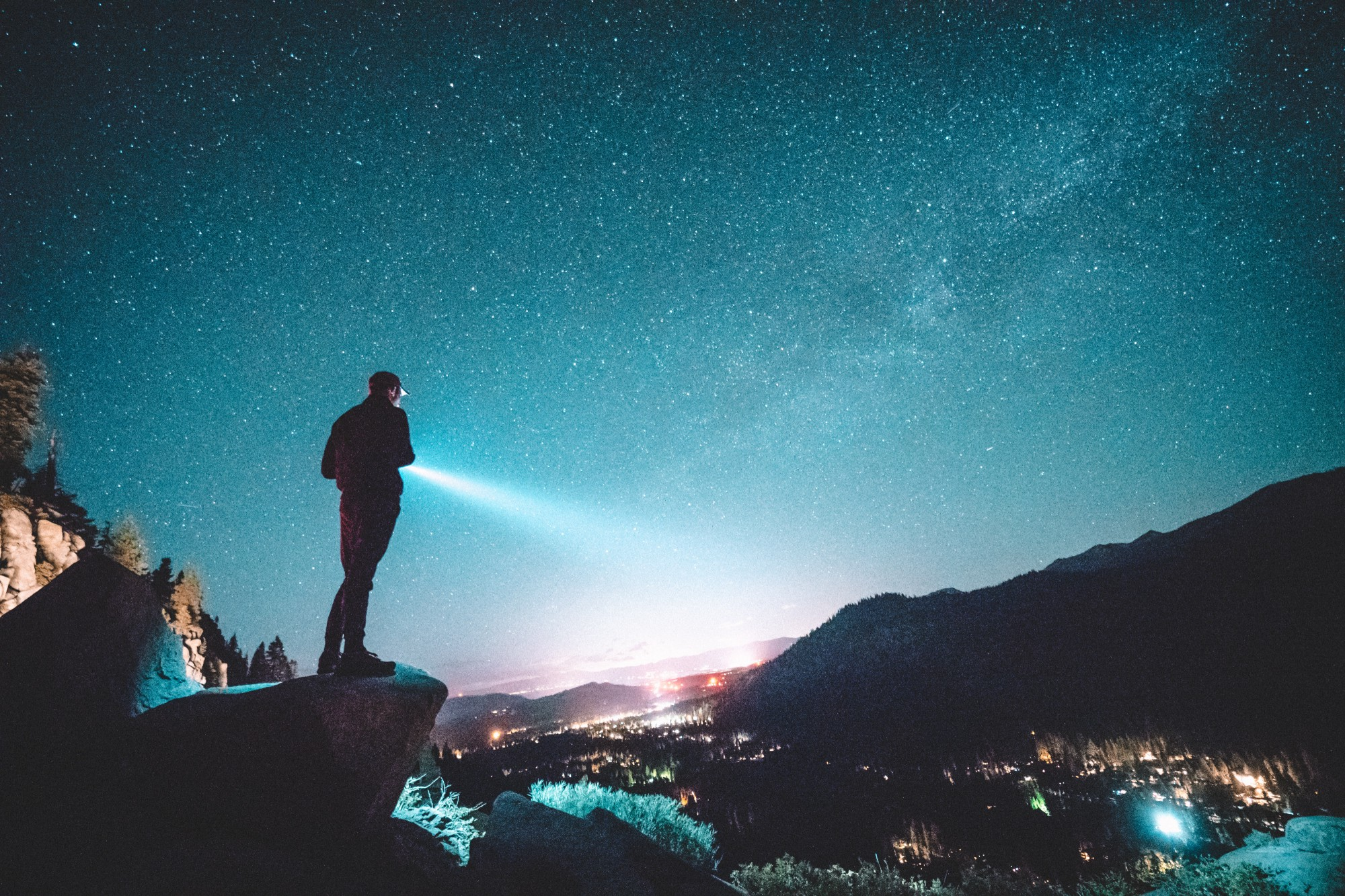 Man standing on mountain, looking out with a flashlight on a valley, under a starry sky.