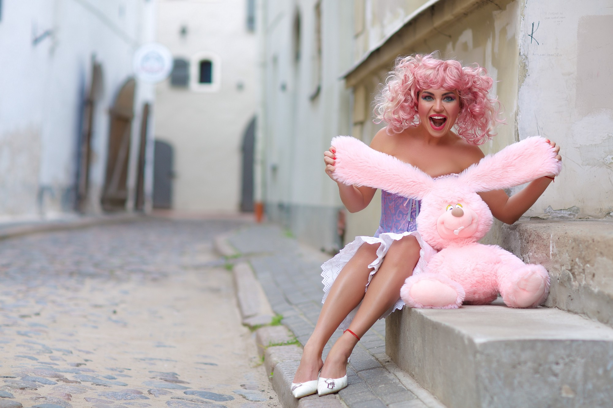 photo of smiling woman holding a pink bunny on a sidewalk