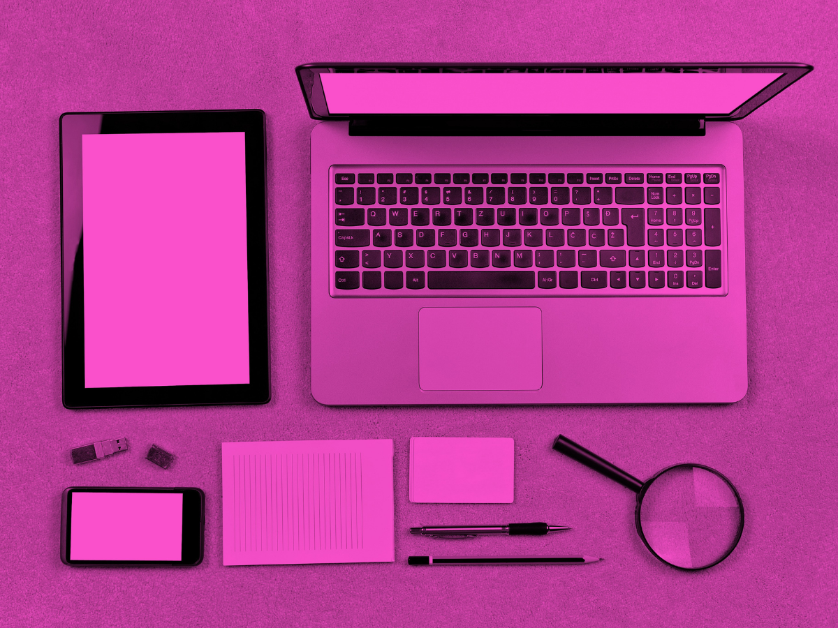 A laptop, tablet, magnifying glass, phone, usb drive, pad of paper, pencil, and pen sitting on a desk