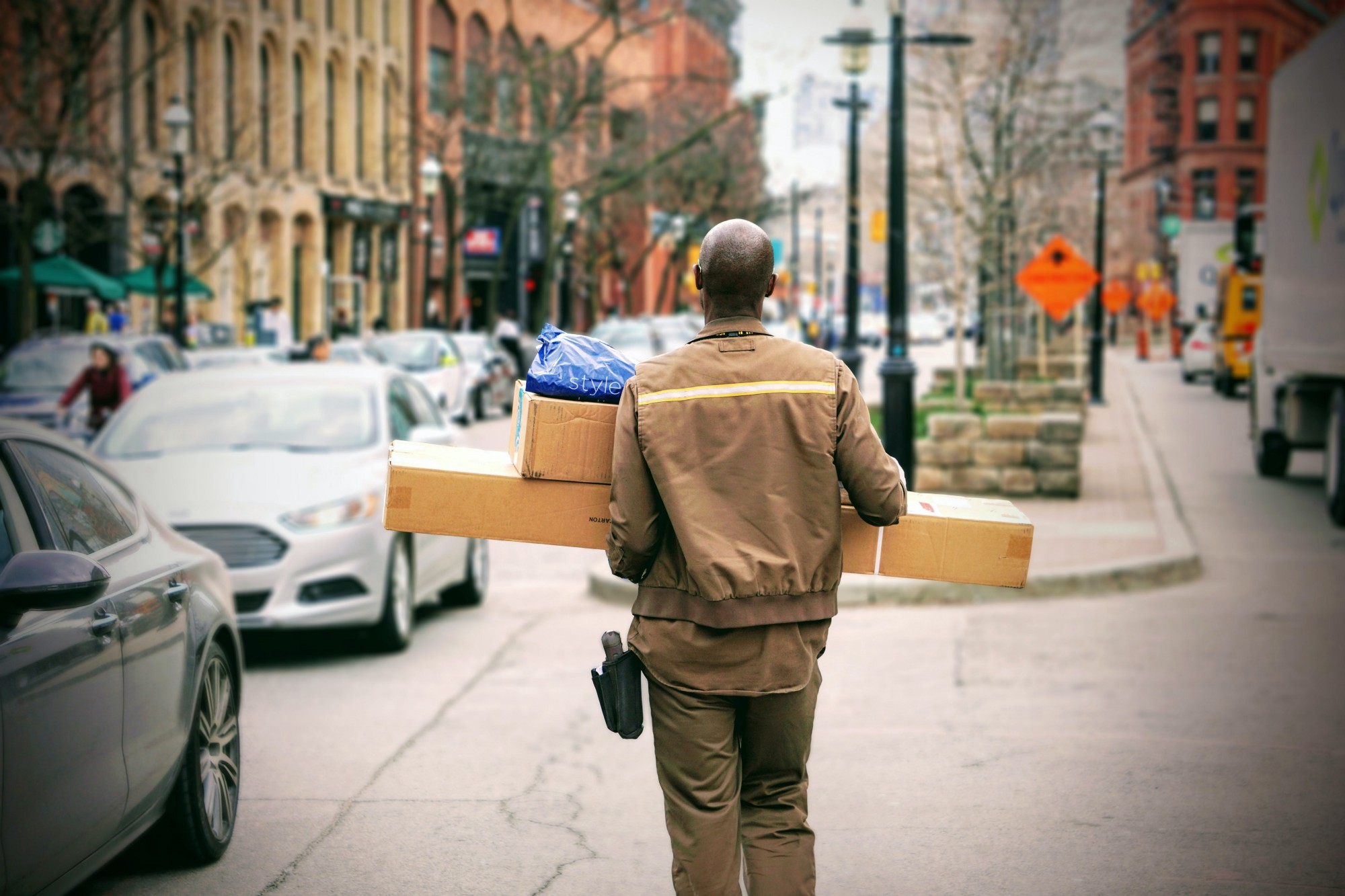 A delivery driver carrying parcels