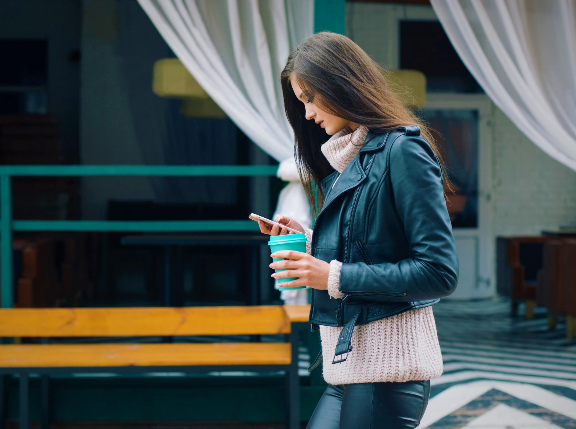 girl with long brown hair wearing black leather jacket holding cell phone and cup of coffee in her hands