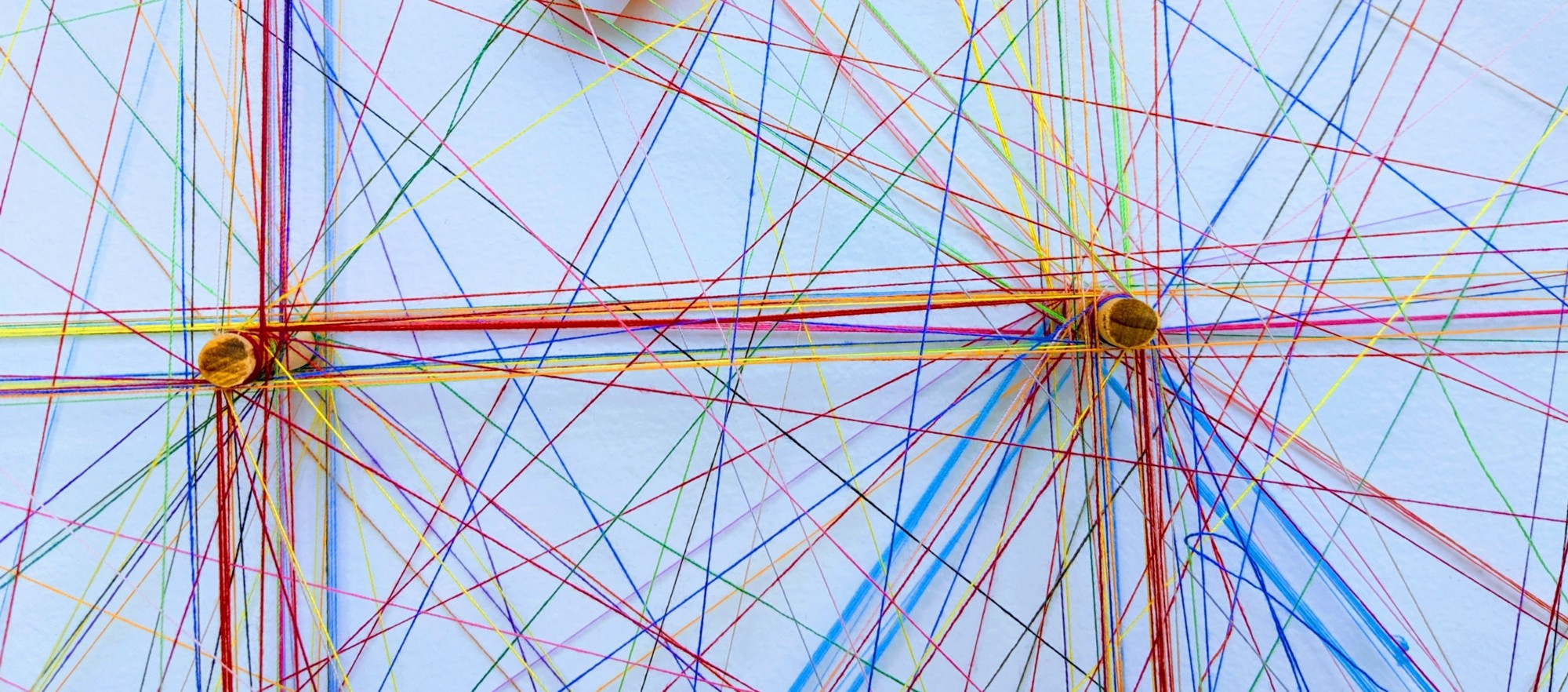 Coloured threads wound around spokes to form a network. Photo by Omar Flores on Unsplash