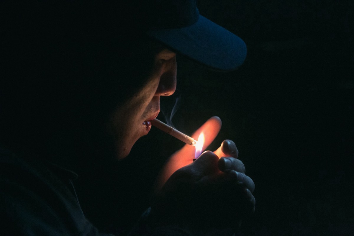 A man in the dark lights a cigarette, and his face is illuminated by the flame.