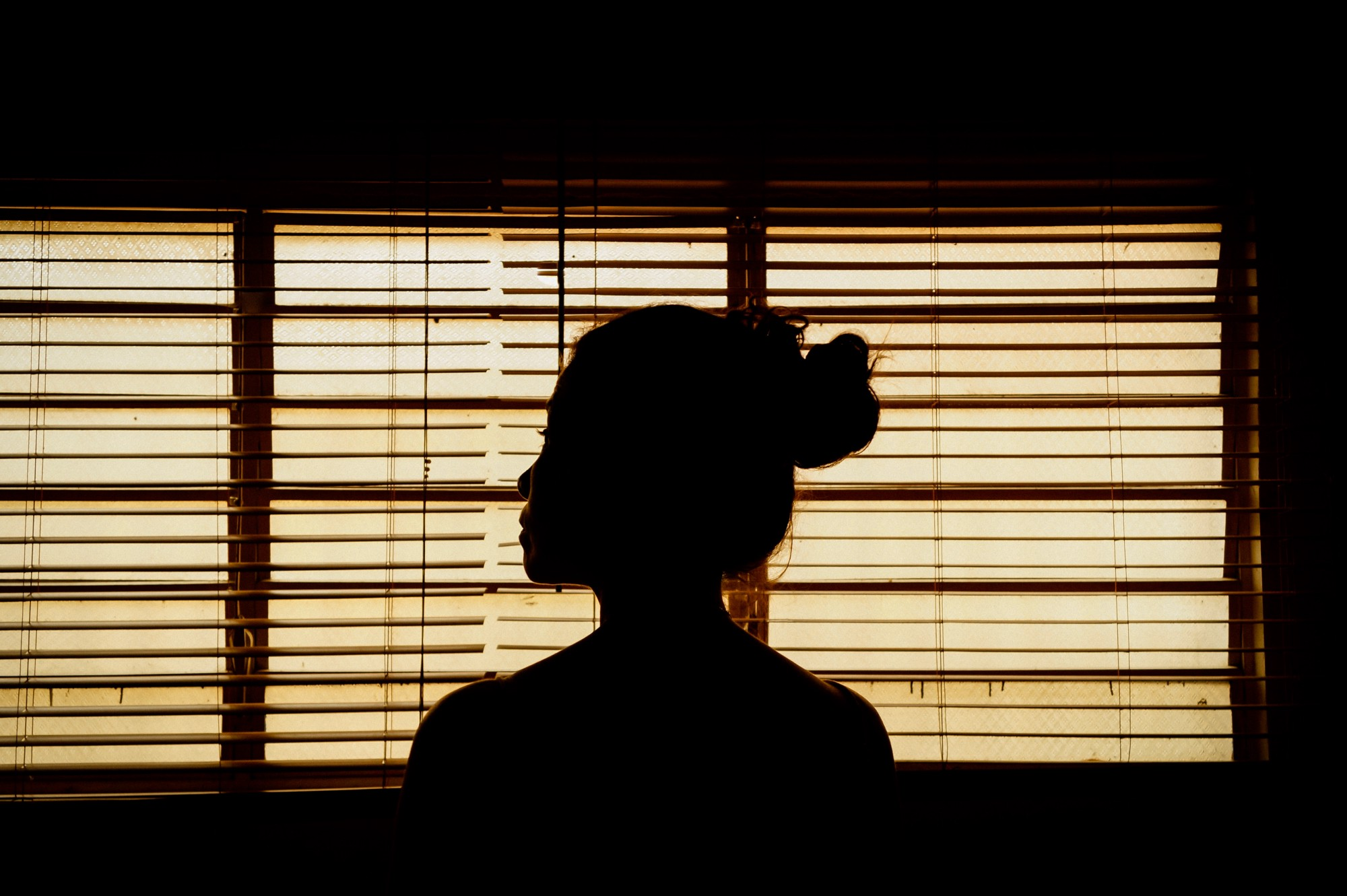 a silhouette of a woman looks out of a window