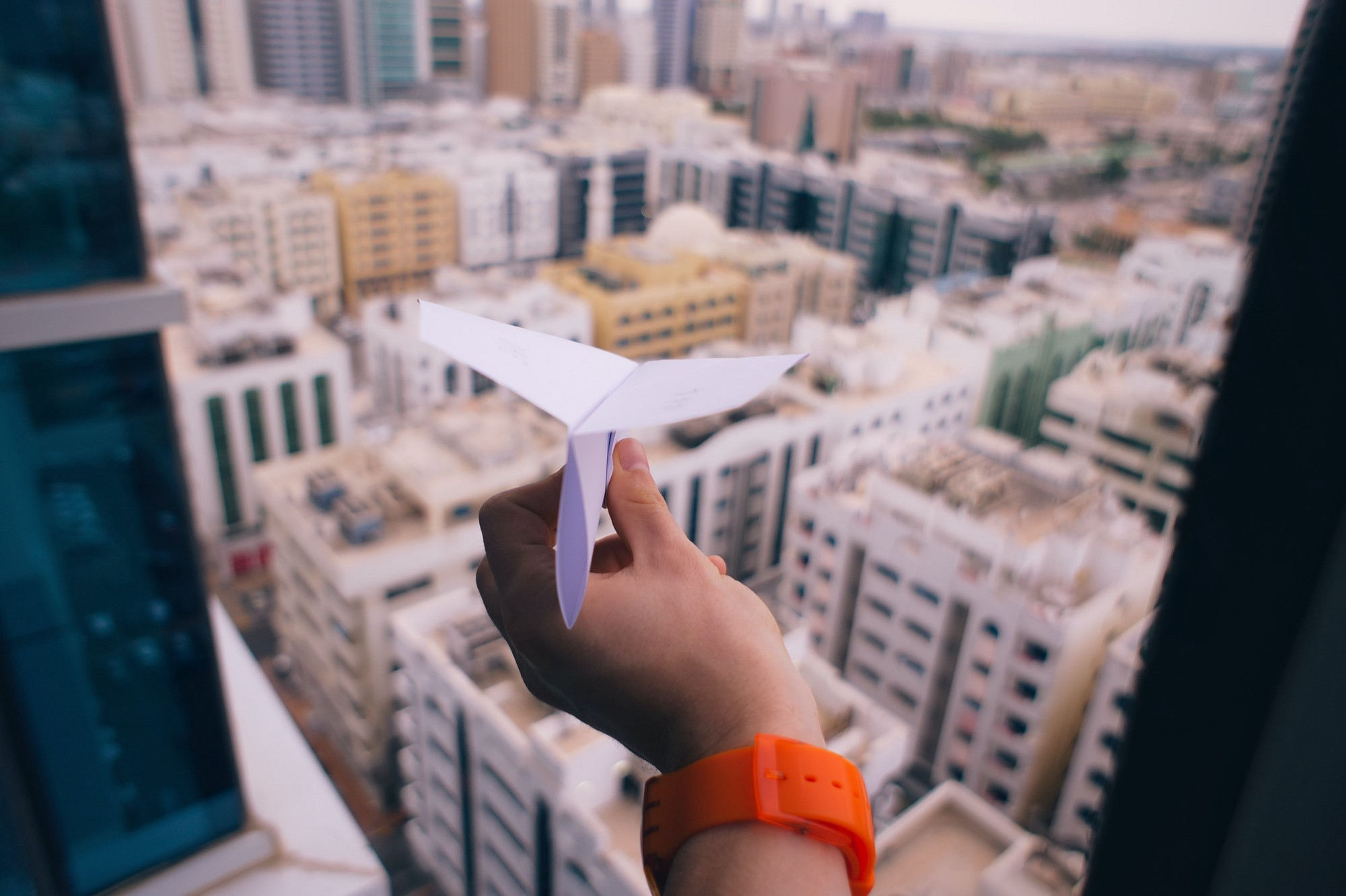 Hand holding paper airplane above city office buildings.