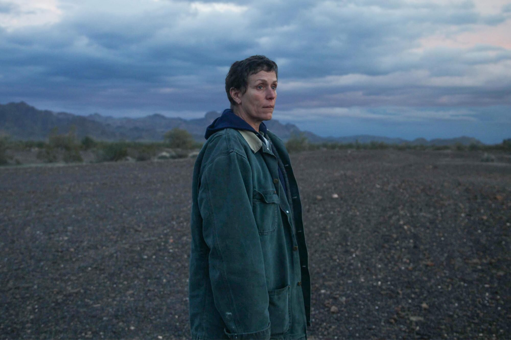 Fern (Frances McDormand) with close-cropped hair, wearing a jean jacket over a dark-colored hoodie, standing on a barren field under a darkening stormy sky.
