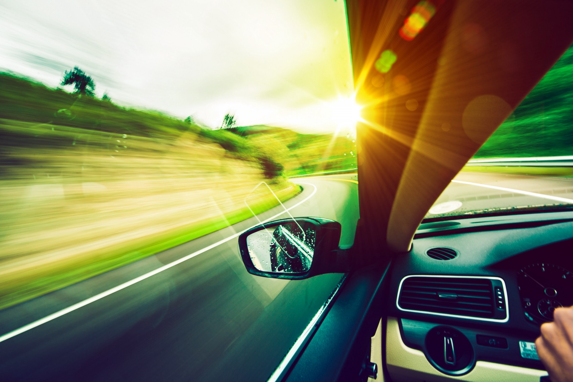 Close-up of car side mirror, racing down the road, sun in the foreground, fantasy-style lighting