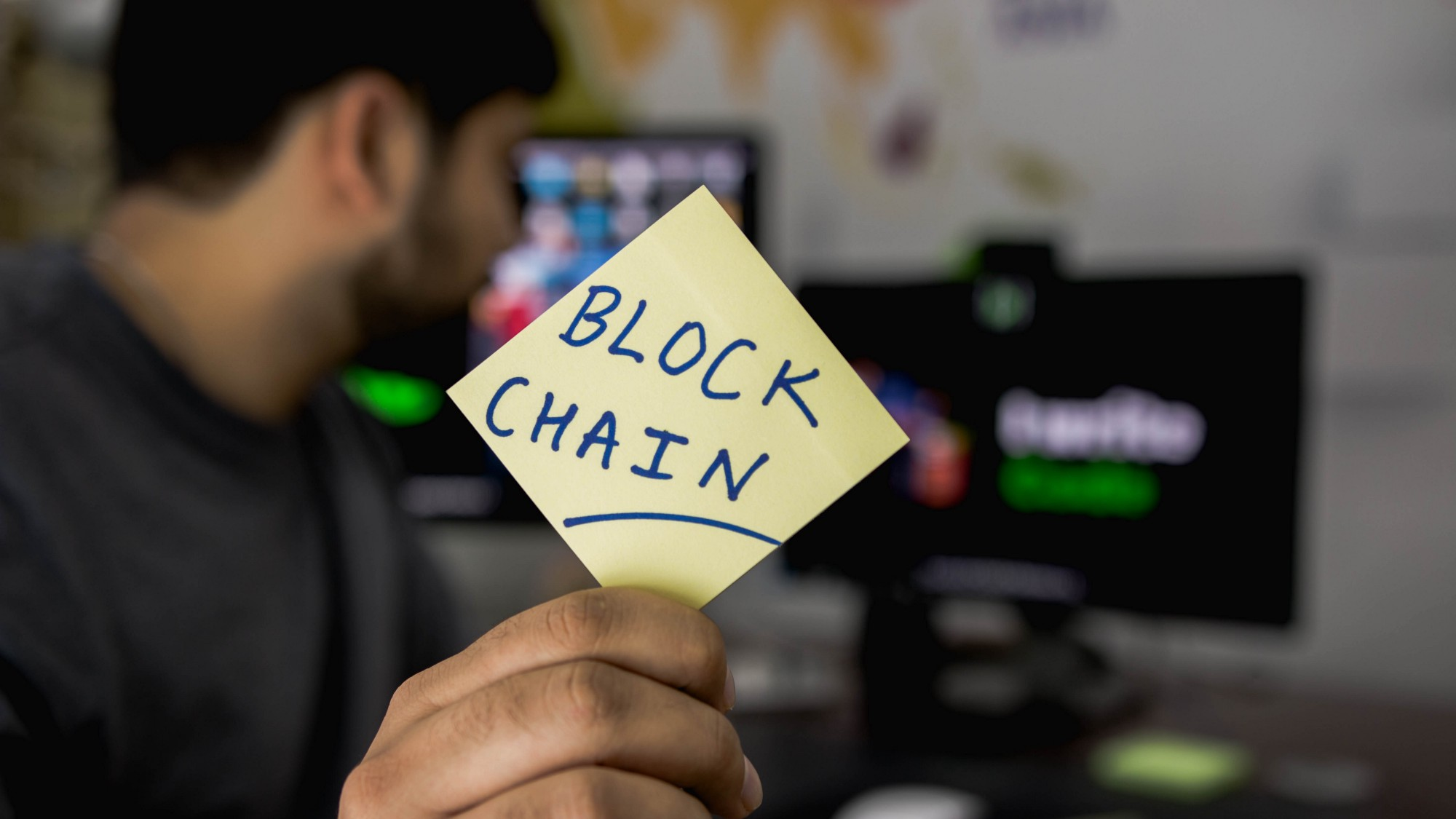 Men holding a sticky note written with the word blockchain