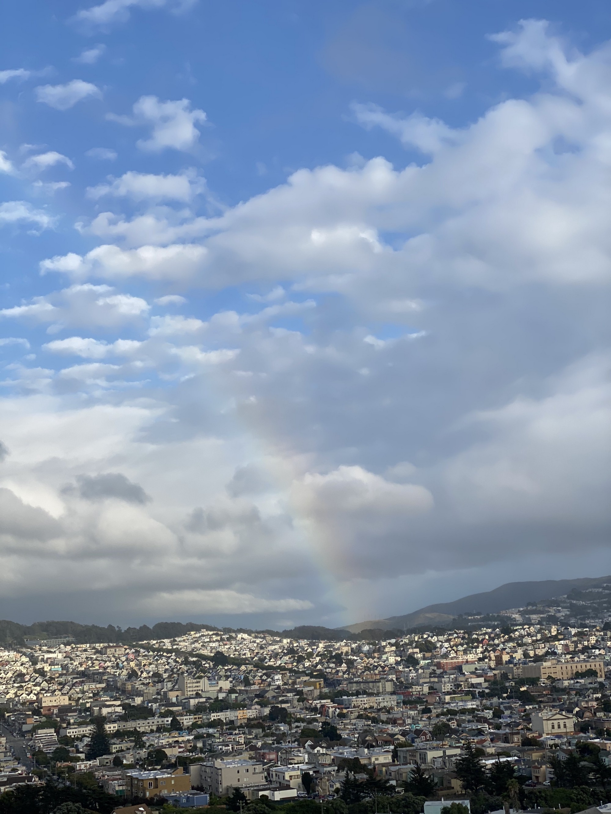 Photo of a beautiful sky with soft white clouds and a rainbow from the sky going in front of a mountain and a town in the valley.