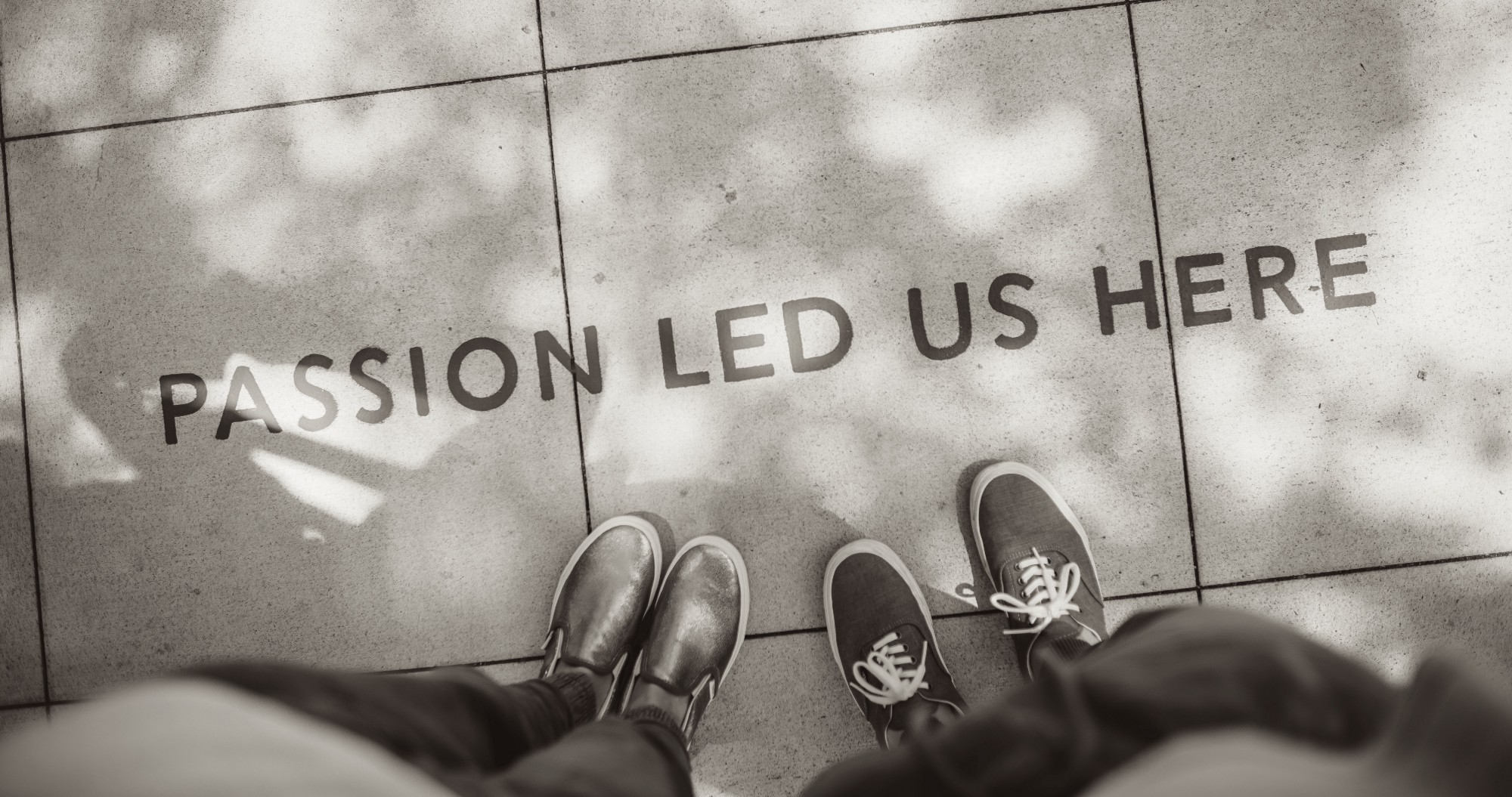 """Photo of two sets of feet standing on a pavement with the text """"Passion led us here""""."""