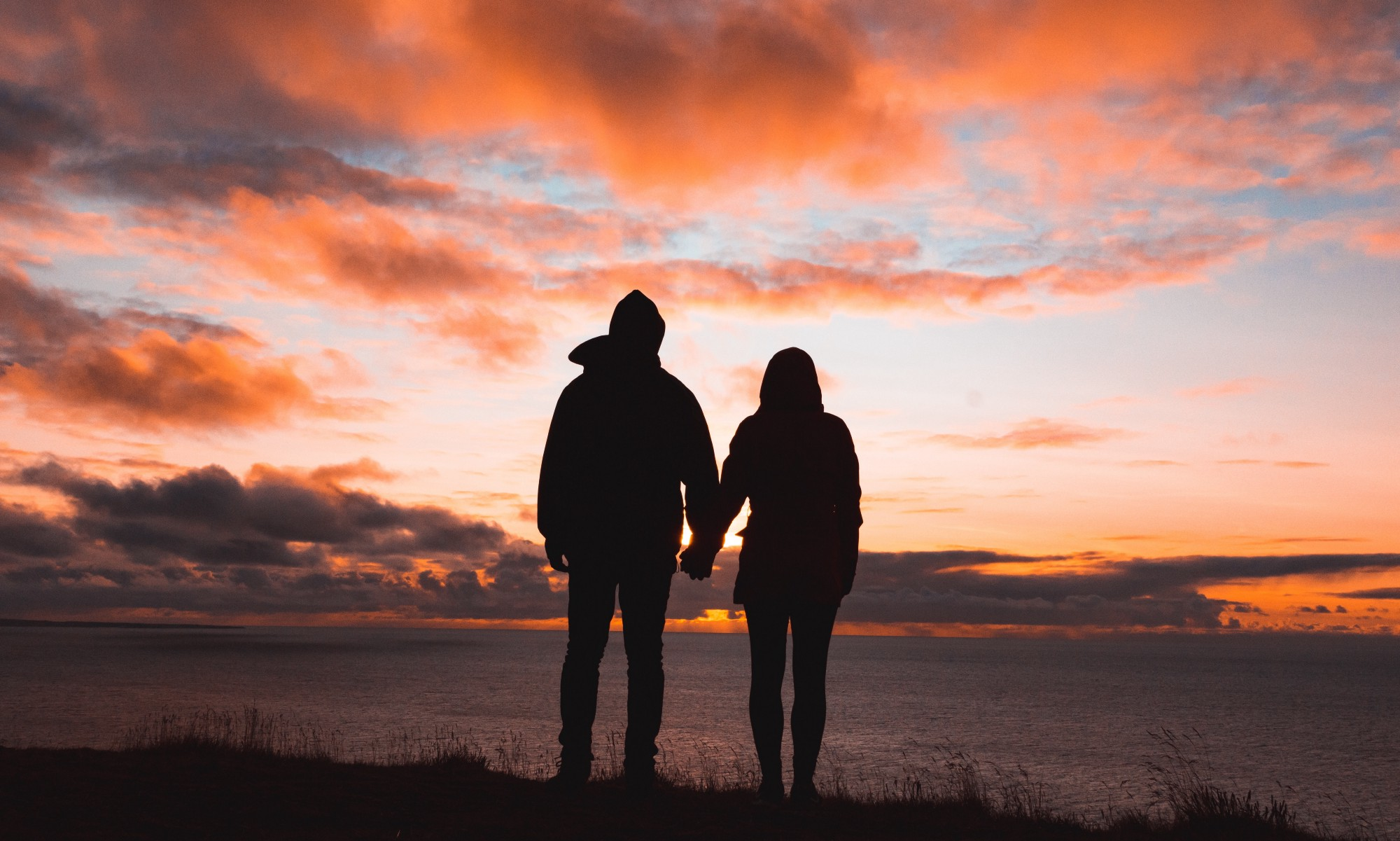 Couple holding hands looking at sunset