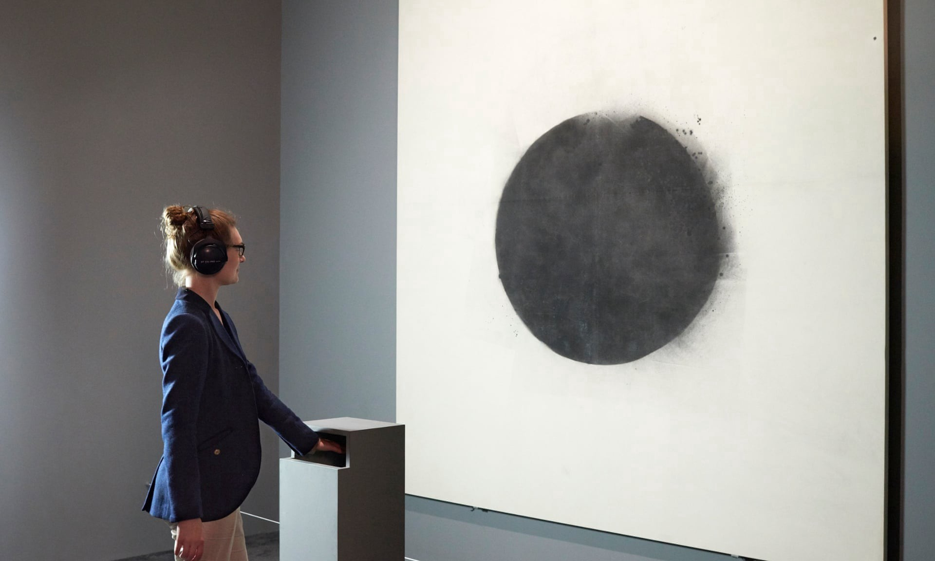 woman touches an equipment that simmulates raindrops, while looks at painting