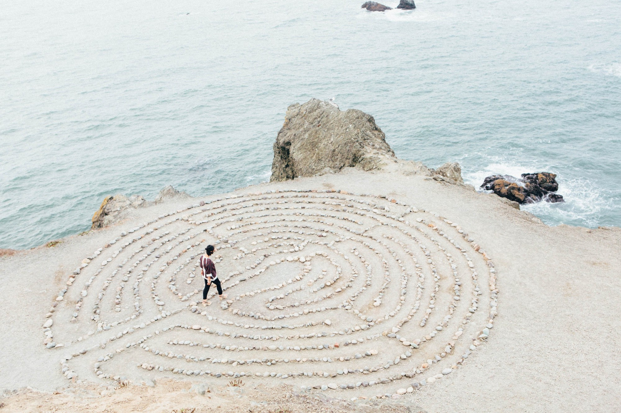 Person's going through the maze on the beach with rocks