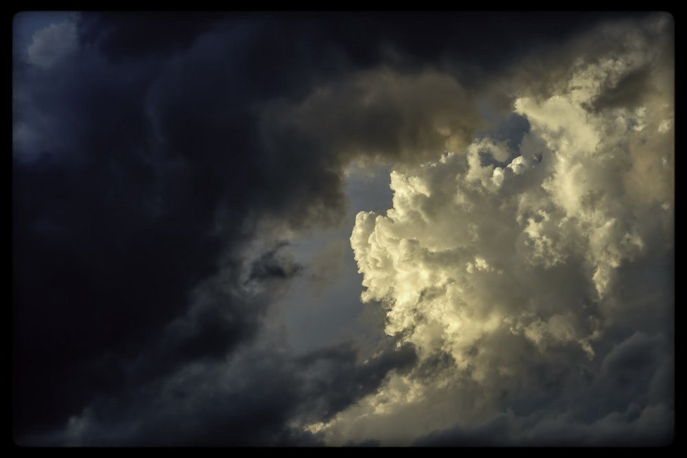 Sky and cloud view, split in half diagonally: black and stormy on left, sunlit and bright on the right.